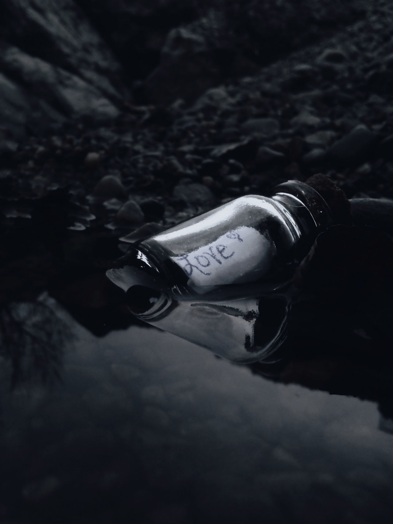 Love is everything :) well and food too, but love is up there lol ;) Bottle Love Love Note Message In A Bottle Monochrome Nature Outdoors PhonePhotography Reflection Rocks Shore Water