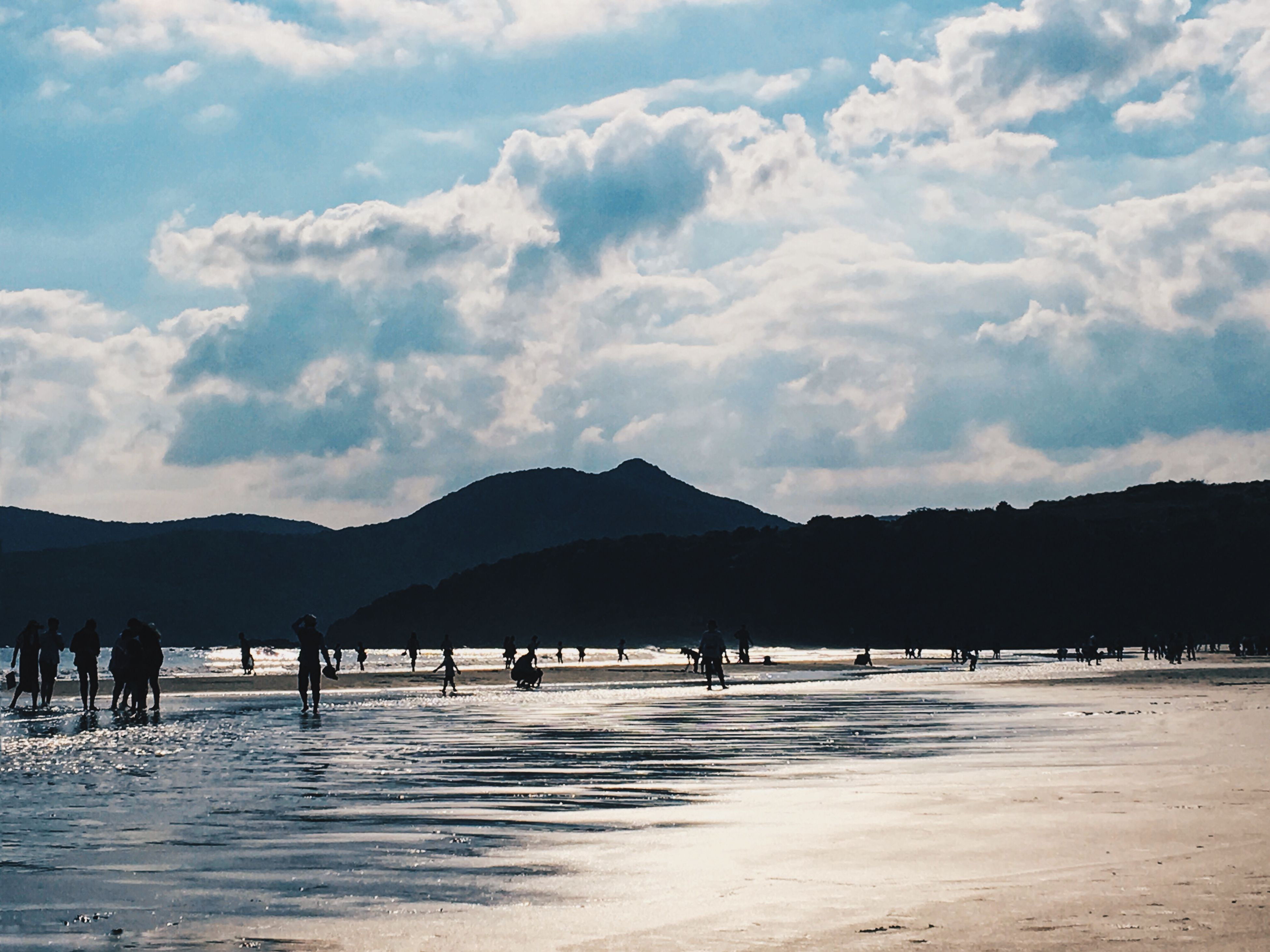mountain, sky, large group of people, water, cloud - sky, beach, scenics, mountain range, beauty in nature, tranquil scene, nature, vacations, leisure activity, sea, tourism, tourist, silhouette, tranquility, sand