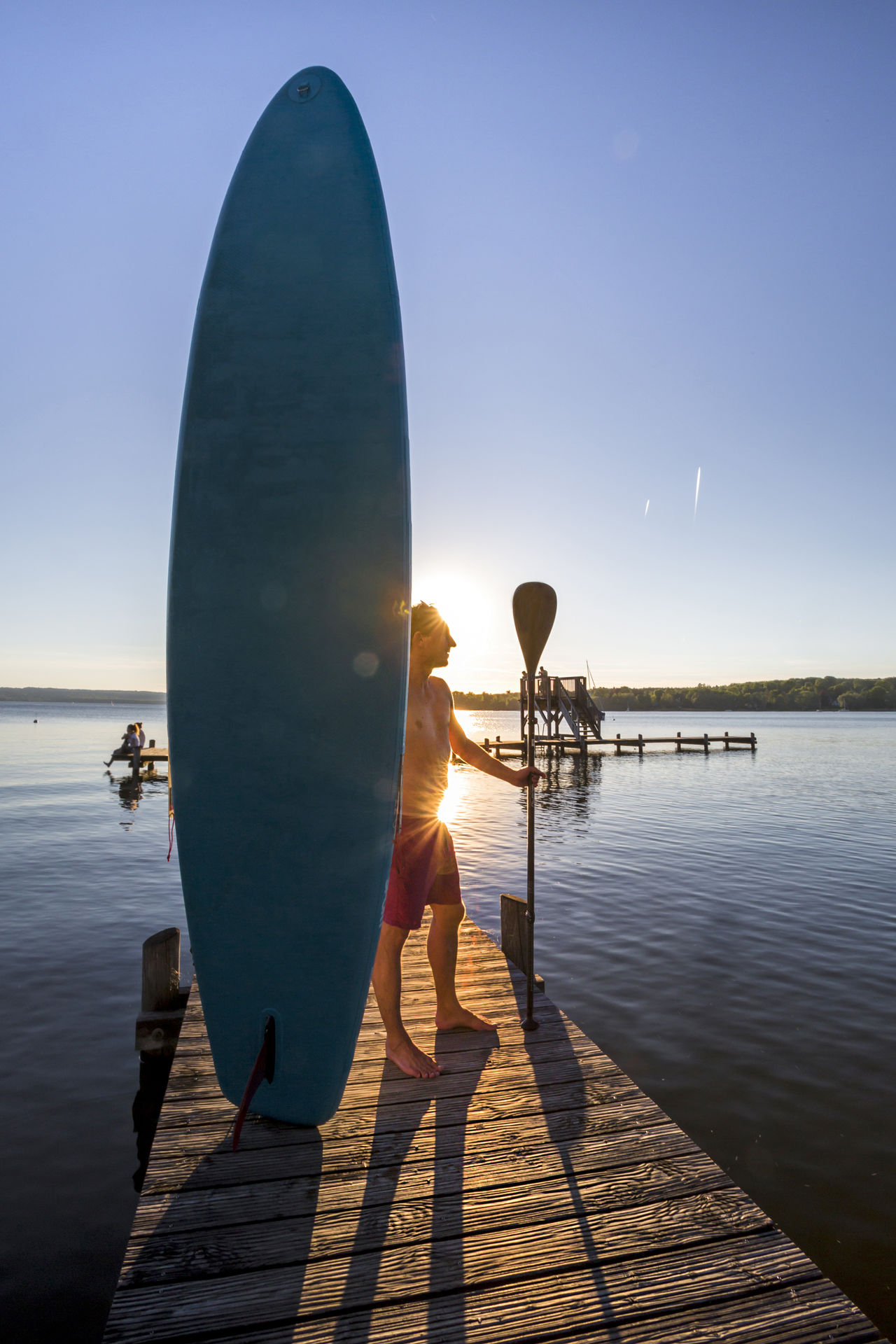 Standup paddler at the lake in sunset Bayern Beach Beauty In Nature Dawn Fitness Footbridge Holiday Lake Leisure Activity Lifestyles Man Outdoors Pier Portrait Recreation  Sports Standup Paddleboarding Standuppaddle Sunset Sup Surfer Travel Unfiltered Water Watersports