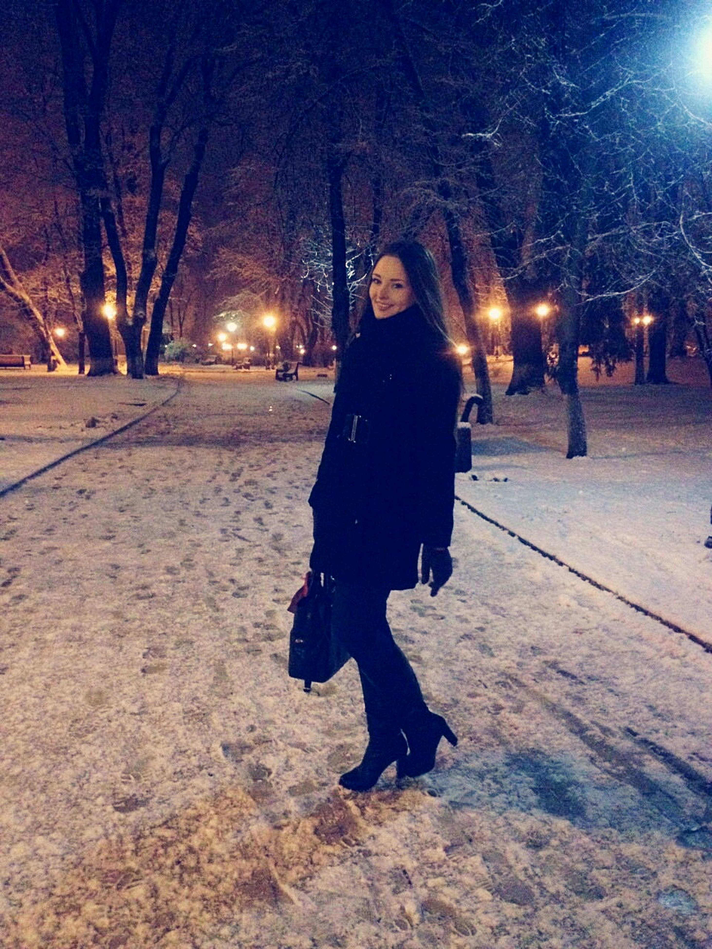 illuminated, night, lifestyles, full length, leisure activity, standing, winter, snow, front view, cold temperature, warm clothing, lighting equipment, casual clothing, season, street, rear view, walking, street light