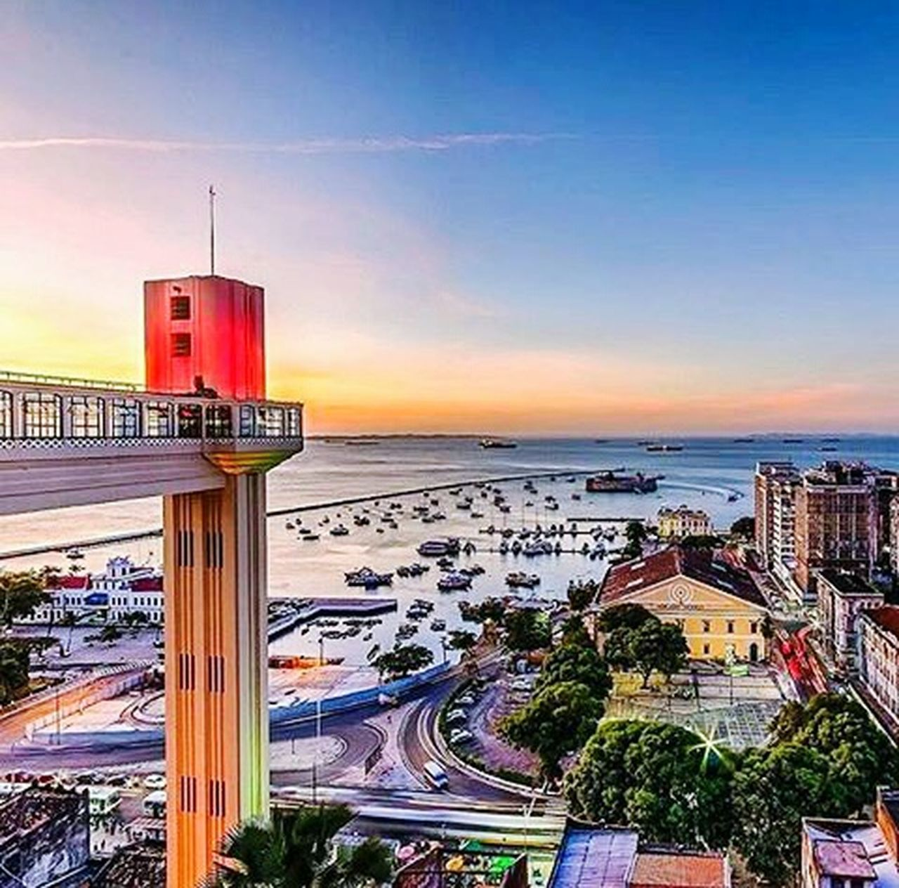 architecture, building exterior, built structure, travel destinations, sunset, city, street, outdoors, transportation, road, sky, horizon over water, cityscape, beach, blue, no people, day, urban skyline
