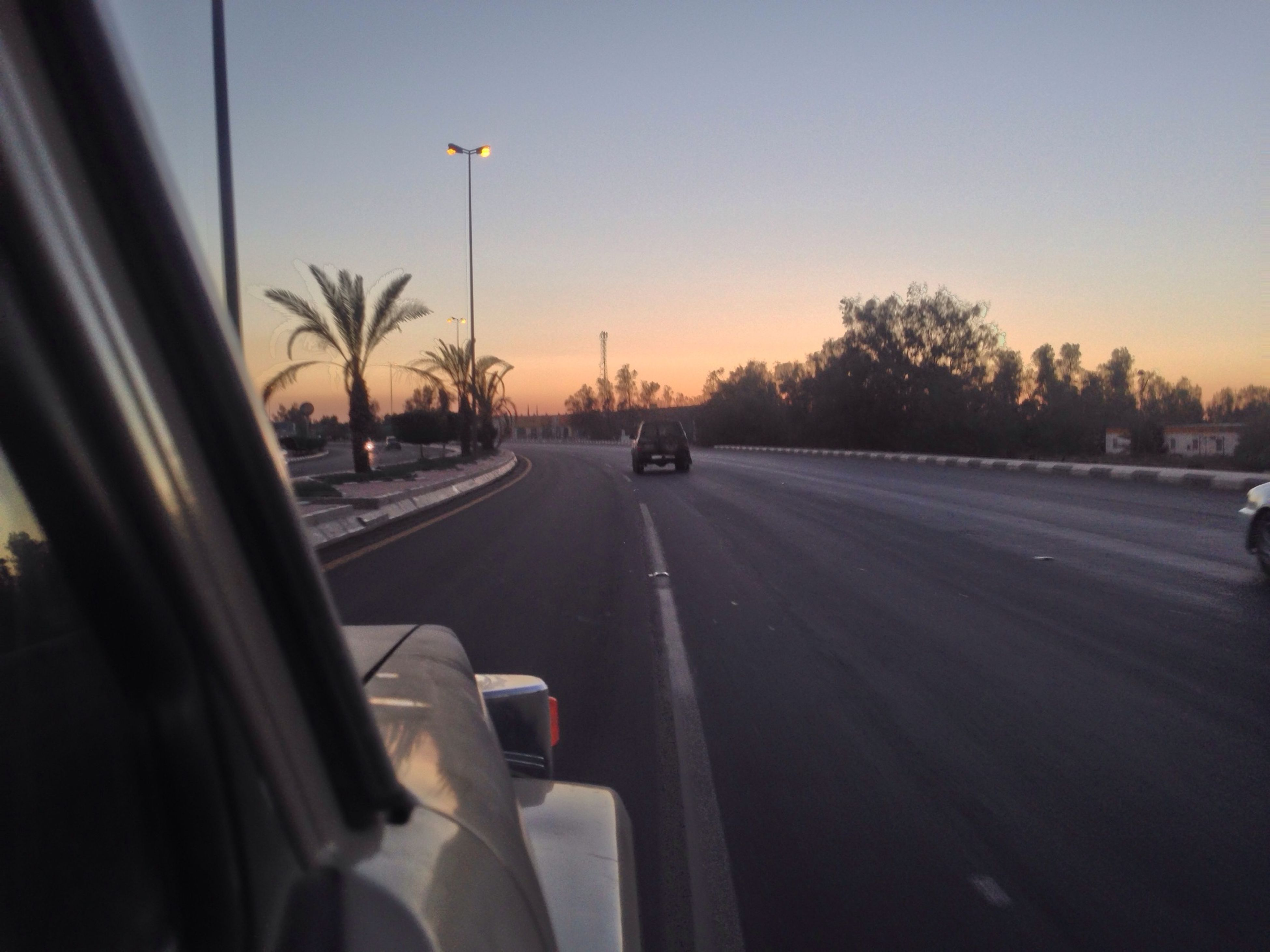 transportation, mode of transport, car, land vehicle, road, on the move, travel, vehicle interior, windshield, sunset, road marking, sky, street, car interior, journey, glass - material, airplane, clear sky, transparent, the way forward