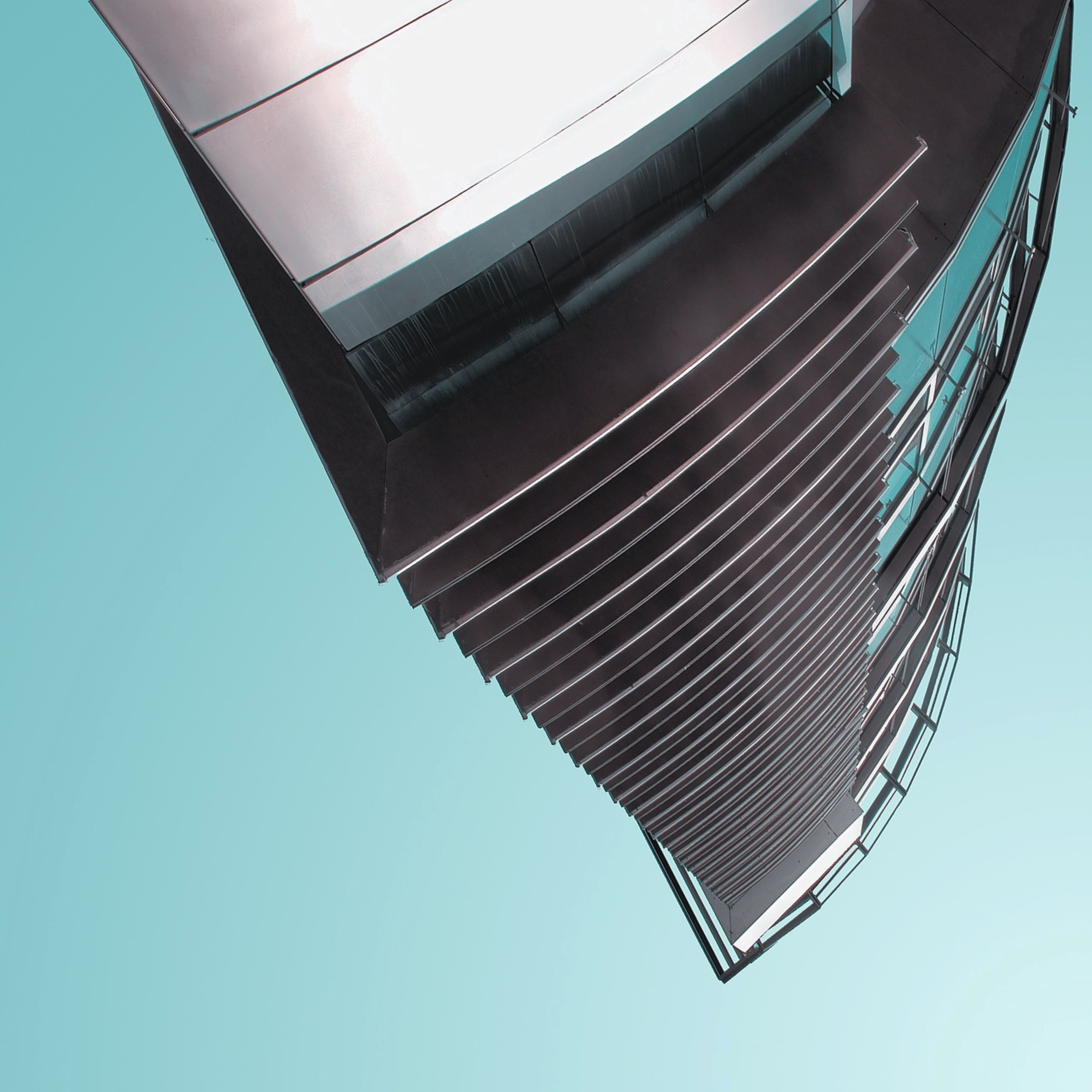low angle view, clear sky, blue, architecture, built structure, directly below, modern, building exterior, copy space, day, pattern, no people, outdoors, part of, building, tall - high, geometric shape, office building, sky, metal