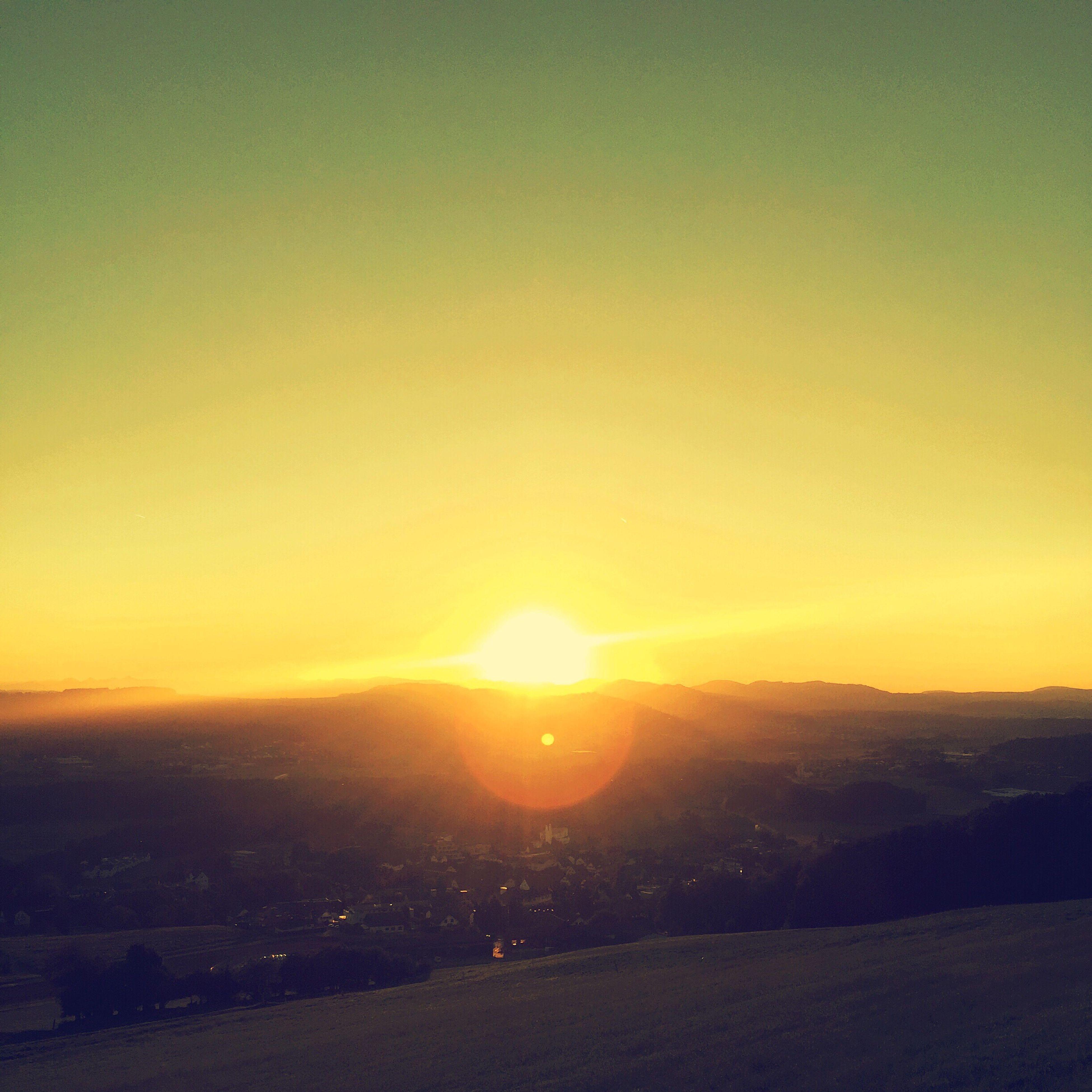 sunset, sun, landscape, tranquil scene, scenics, sunlight, beauty in nature, orange color, tranquility, nature, mountain, sunbeam, vibrant color, lens flare, sky, majestic, bright, dark, outdoors, rural scene, non-urban scene, no people, outline, solitude, dramatic sky, mountain range, remote