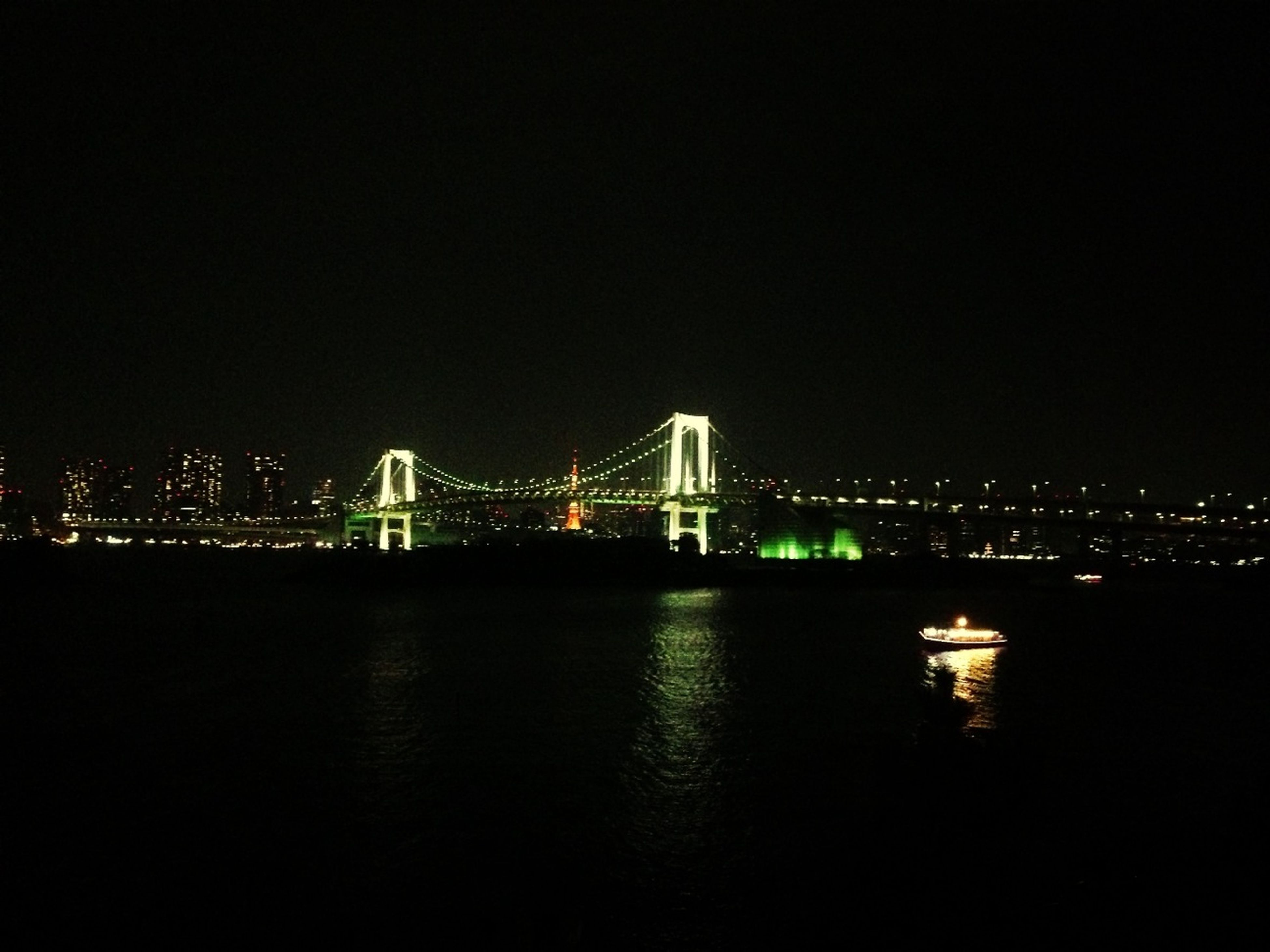 illuminated, night, water, architecture, built structure, city, river, copy space, waterfront, connection, bridge - man made structure, cityscape, building exterior, clear sky, reflection, sea, bridge, dark, suspension bridge, engineering