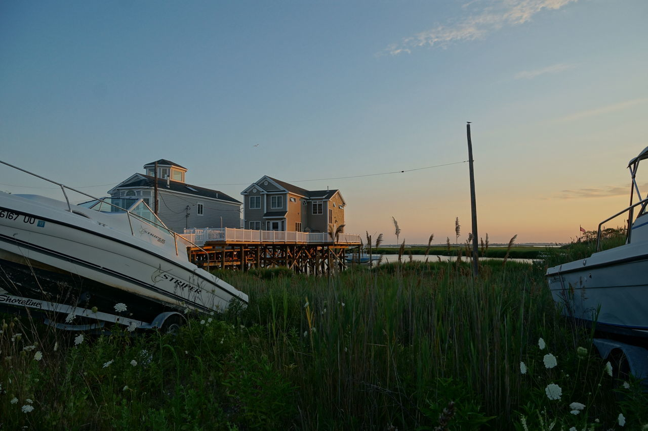 Sunset over Jamaica Bay, New York City Boat Building Exterior Day Evening Evening Sunlight Flowers Grass House Jamaica Bay Meadow New York City No People Outdoors Peaceful Power Line  Sky Suburbia Summer Sunlight Sunset Tranquil Scene Tranquility Twilight Water Waterfront