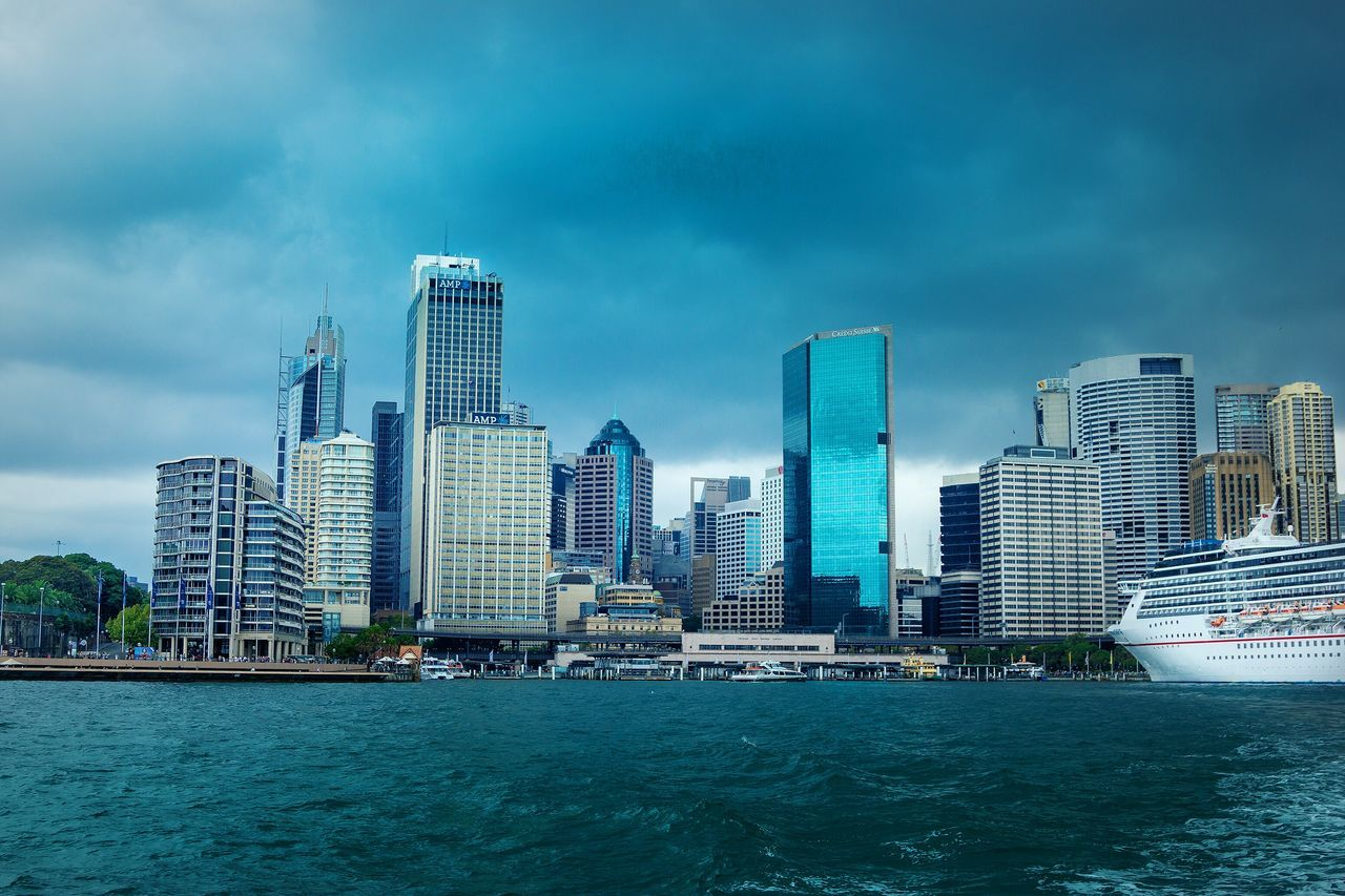 architecture, skyscraper, building exterior, city, built structure, modern, cityscape, tower, waterfront, skyline, water, urban skyline, sky, downtown district, sea, financial district, outdoors, tall, travel destinations, no people, day