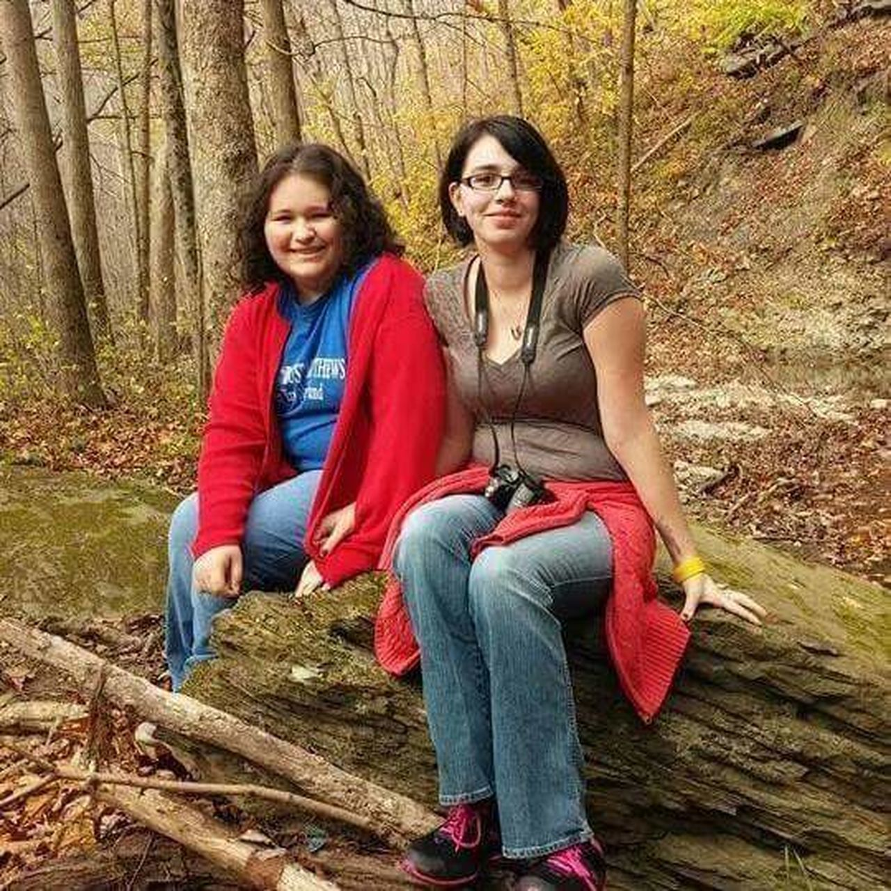 two people, sitting, smiling, mature adult, togetherness, forest, mature women, outdoors, happiness, day, women, real people, portrait, full length, tree, adult, looking at camera, leisure activity, casual clothing, tree trunk, autumn, cheerful, people, nature, only women, adults only, friendship, young adult