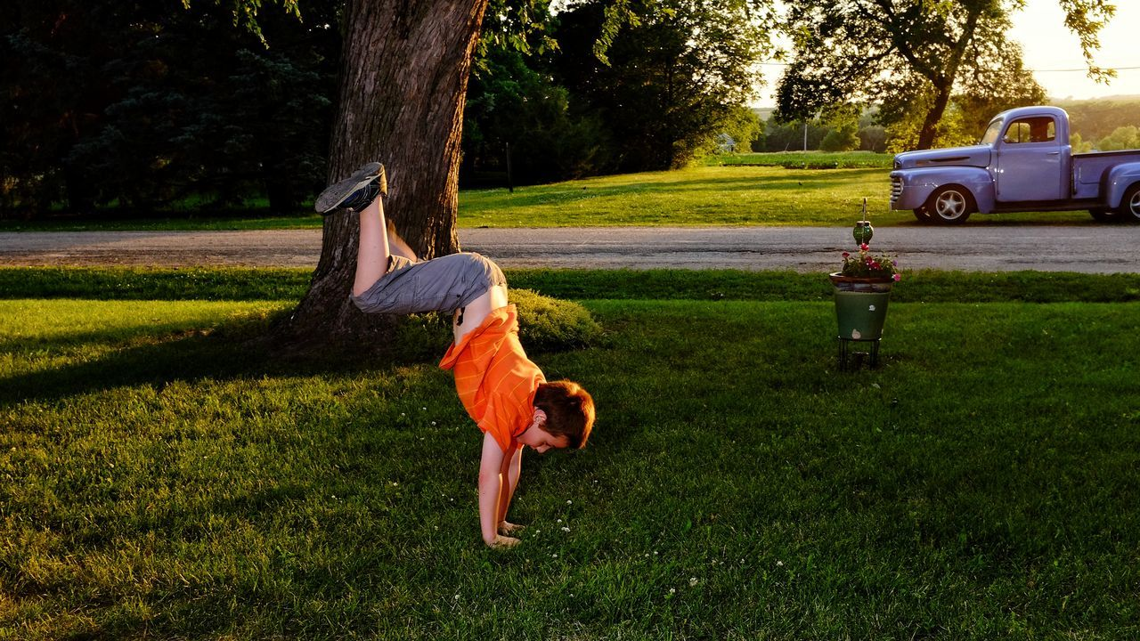 Boy Doing Handstand On Grassy Field At Park