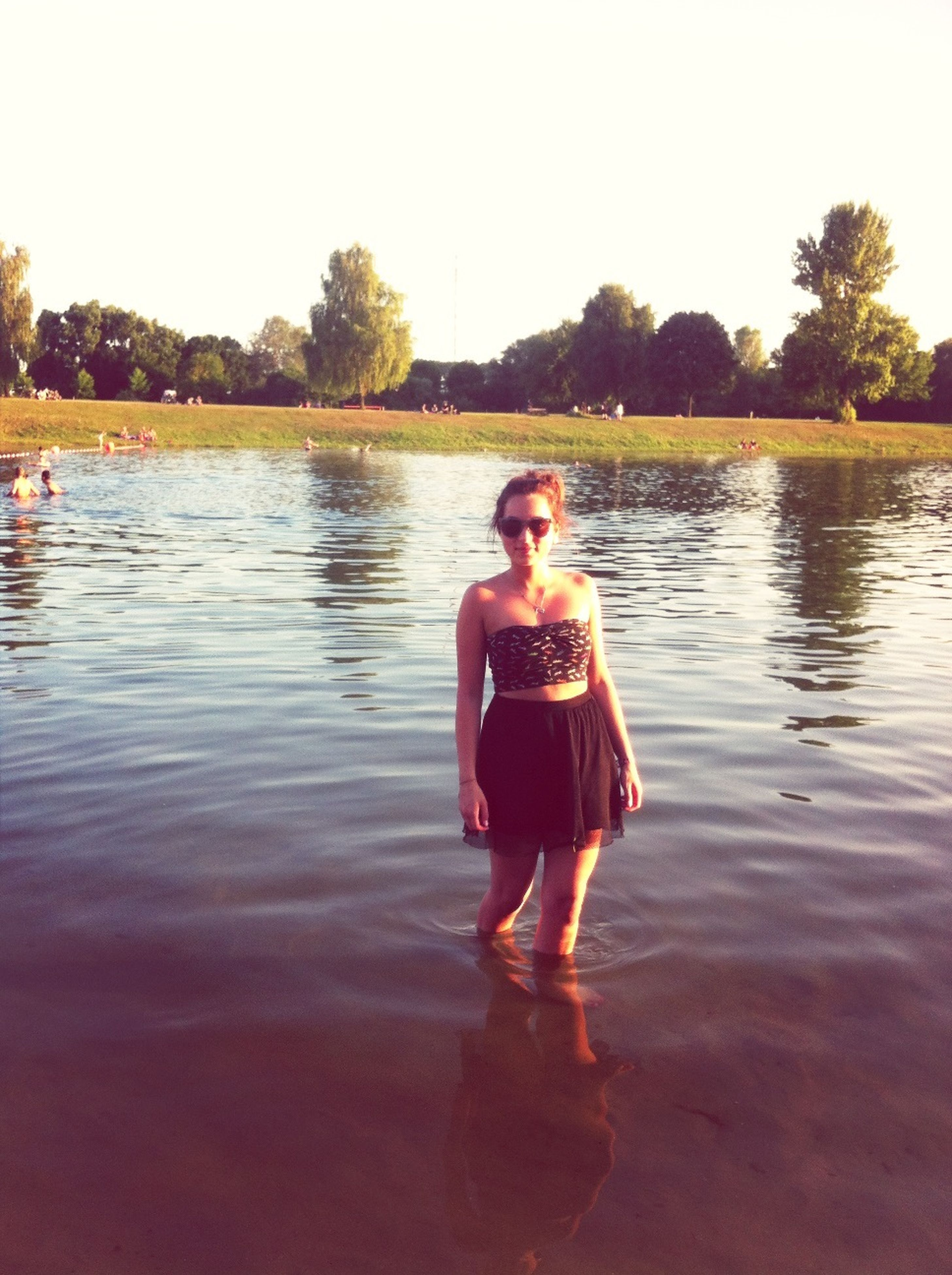 water, lifestyles, person, leisure activity, young adult, lake, full length, casual clothing, waterfront, tree, reflection, looking at camera, portrait, river, vacations, young women, enjoyment, standing