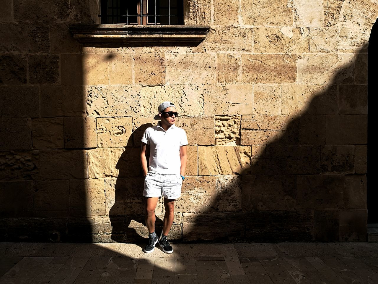real people, one person, built structure, lifestyles, architecture, full length, building exterior, leisure activity, young men, shadow, young adult, day, casual clothing, outdoors, standing, sunlight, men