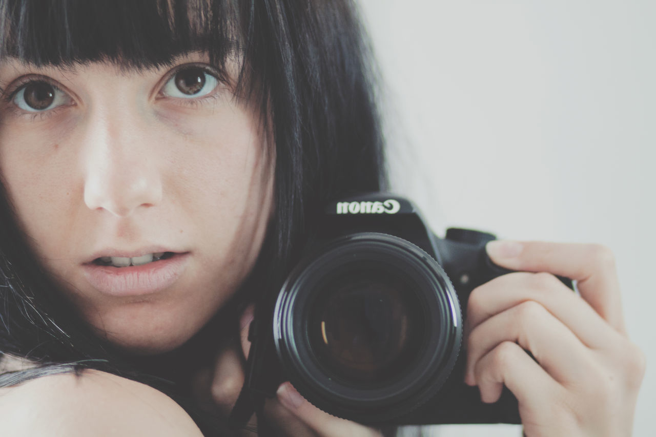 real people, one person, headshot, front view, holding, camera - photographic equipment, photography themes, leisure activity, looking at camera, childhood, close-up, elementary age, lifestyles, portrait, indoors, photographing, technology, young women, digital single-lens reflex camera, young adult, day