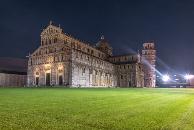 Pisa, Italy - October 22, 2016: Tourists visiting the Leaning Tower of Pisa and Pisa Cathedral in Italy. The Tower of Pisa is one of Italy's most iconic tourist attractions and is famous worldwide for its unintended tilt. Architecture Building Exterior City Fame Government Grass History Landscape Night No People Outdoors Pisa Pisa Tower Pisa, Italy Sky Space Summer Travel Travel Destinations
