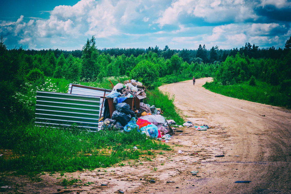 Garbage on the road in the village. Installed waste bins along the road to the village. Rear panel fences knocked down. Rubbish probably have not exported. Garbage Landscape Nature Outdoors Road Tree