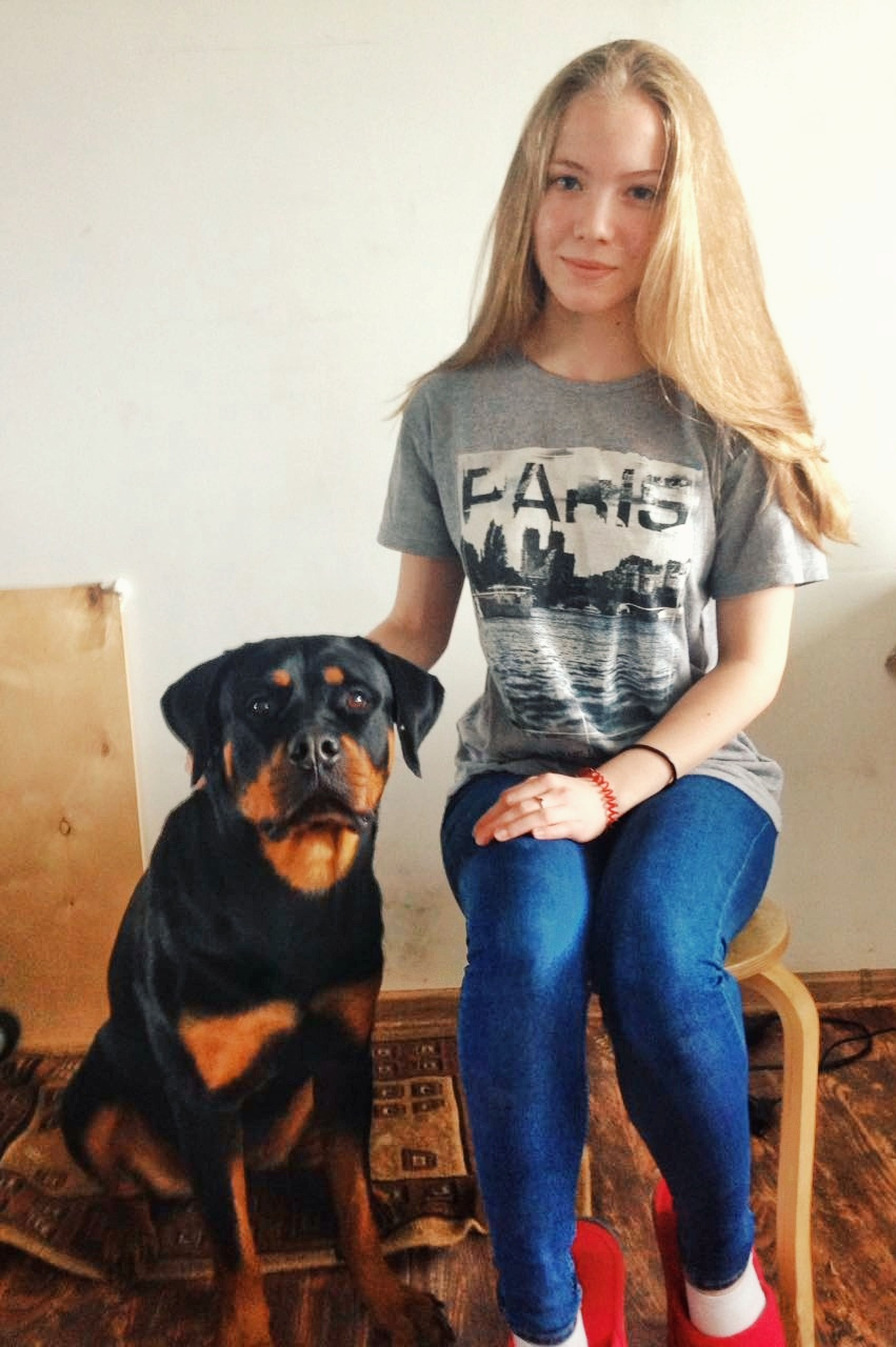 dog, casual clothing, pets, one person, sitting, real people, one animal, animal themes, front view, domestic animals, looking at camera, full length, standing, portrait, young adult, young women, day, indoors, mammal