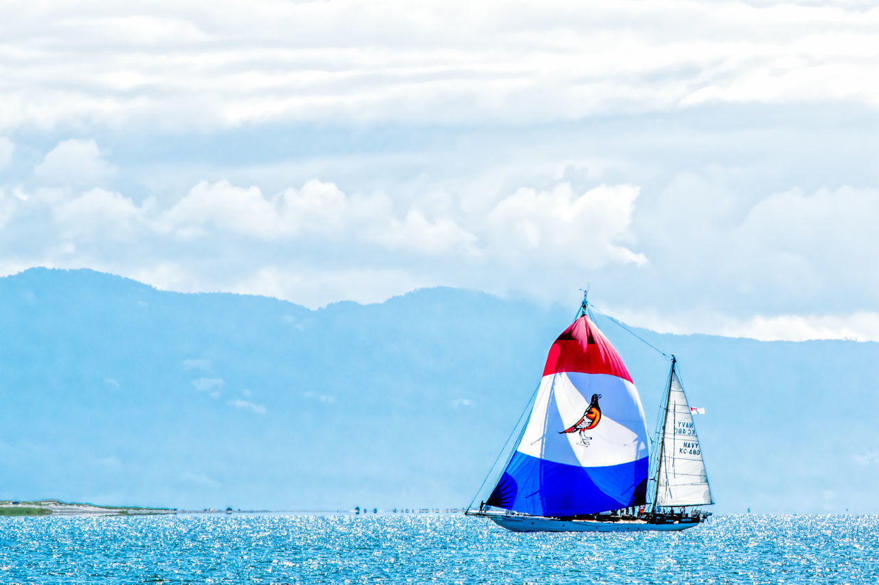 Blue Boat Calm Cloud Cloud - Sky Coastline Day Mode Of Transport Mountain Mountain Range Nature Nautical Vessel Ocean Outdoors Red Sail Sailboat Scenics Sea Sky Tranquil Scene Tranquility Transportation Water Waterfront