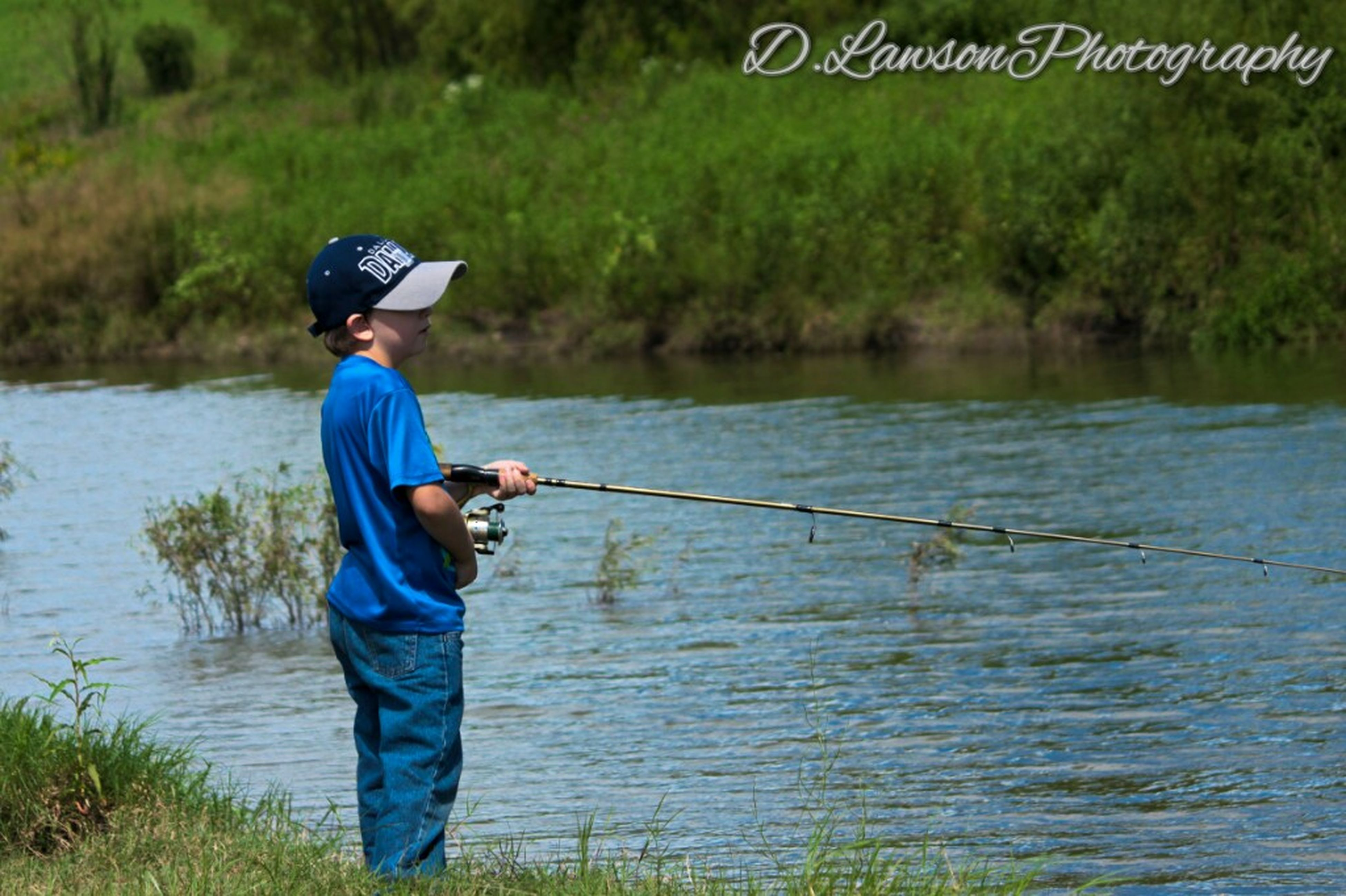 water, casual clothing, full length, grass, leisure activity, lake, boys, lifestyles, side view, childhood, fishing, elementary age, hobbies, holding, standing, plant, person, vacations, nature, day, green color