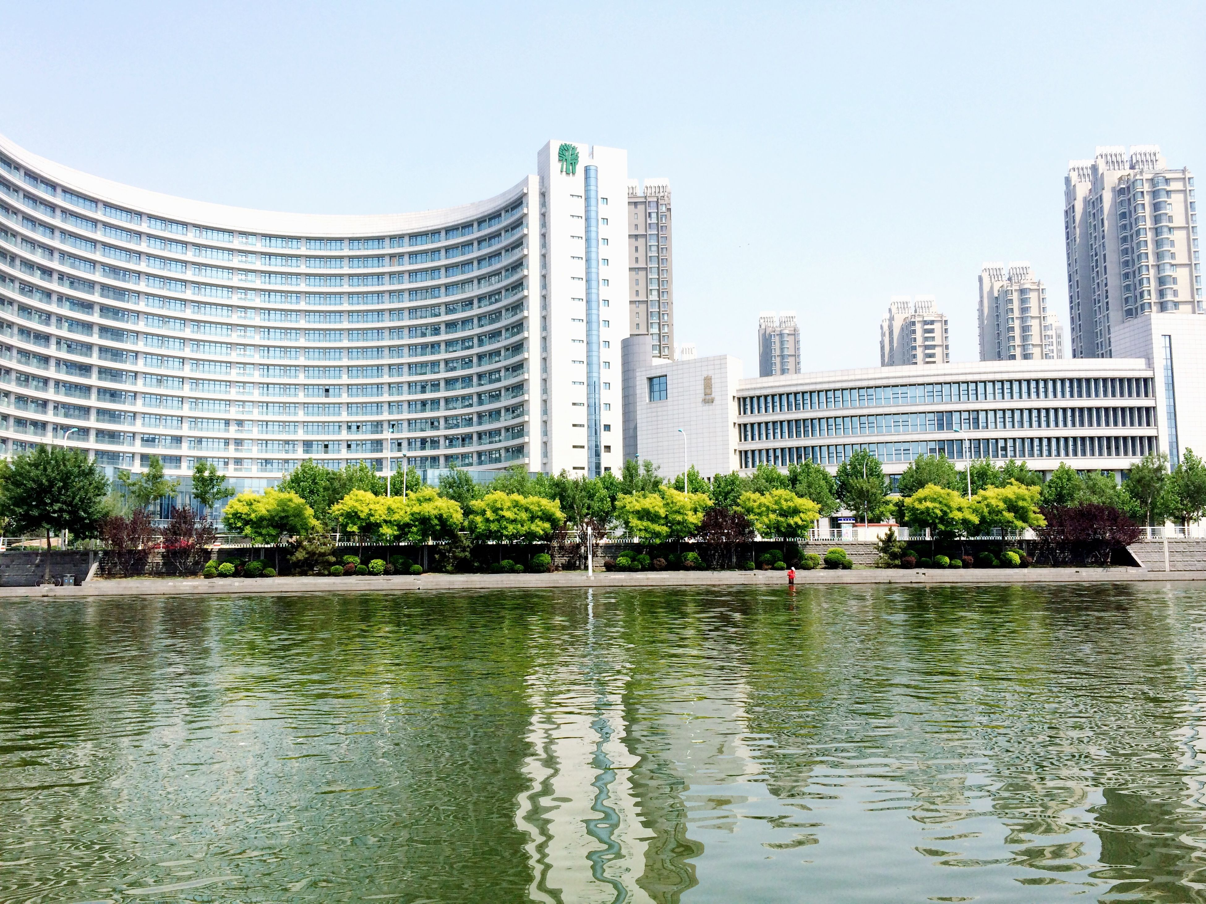building exterior, architecture, built structure, water, city, reflection, clear sky, waterfront, modern, office building, skyscraper, tree, building, tower, tall - high, river, city life, growth, sky, cityscape