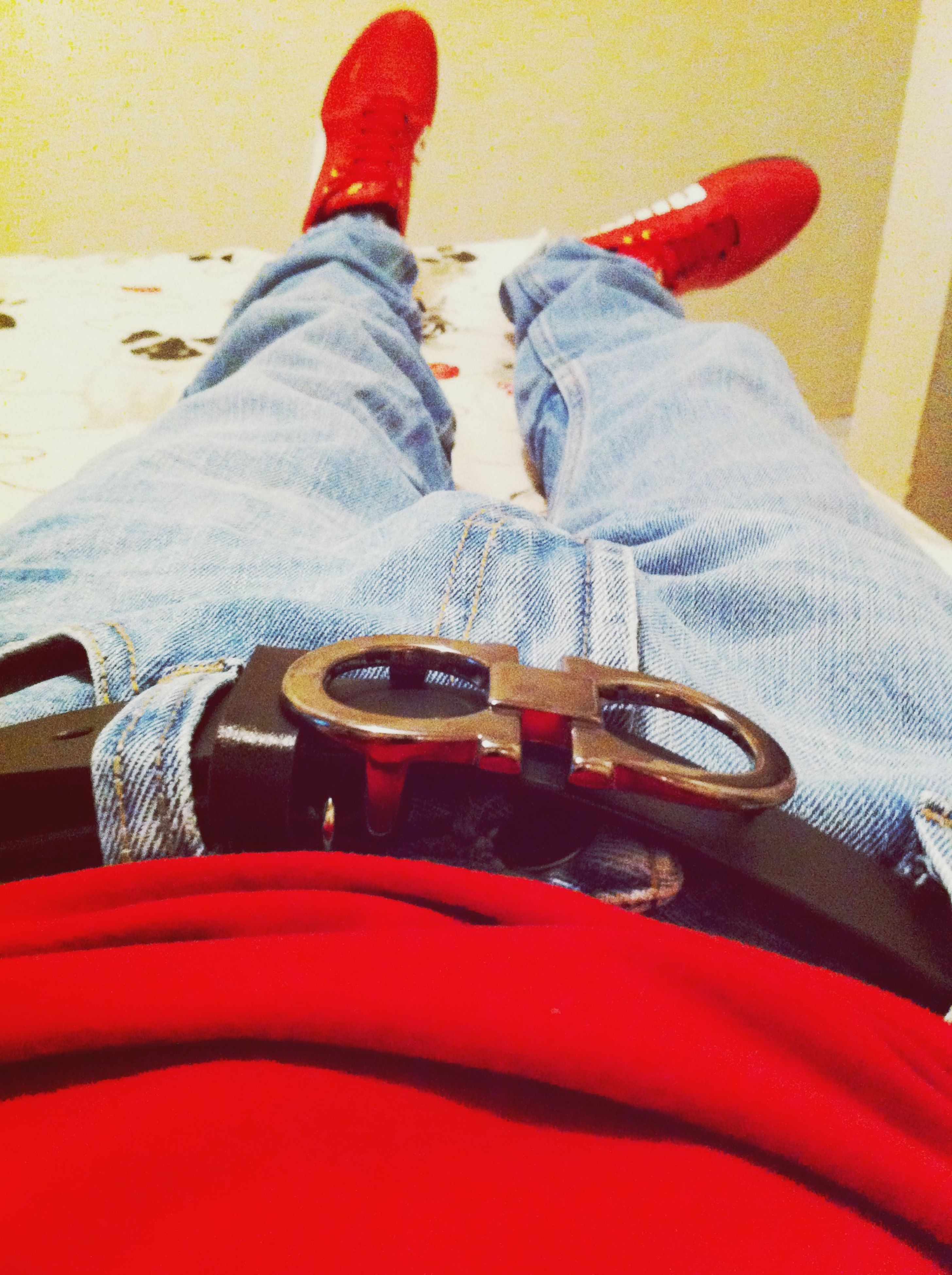 low section, person, shoe, jeans, sitting, footwear, red, lifestyles, men, indoors, casual clothing, human foot, standing, leisure activity, relaxation, personal perspective, canvas shoe