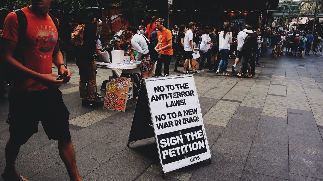 text, real people, large group of people, street, women, men, communication, outdoors, day, protestor, lifestyles, placard, city, crowd, people