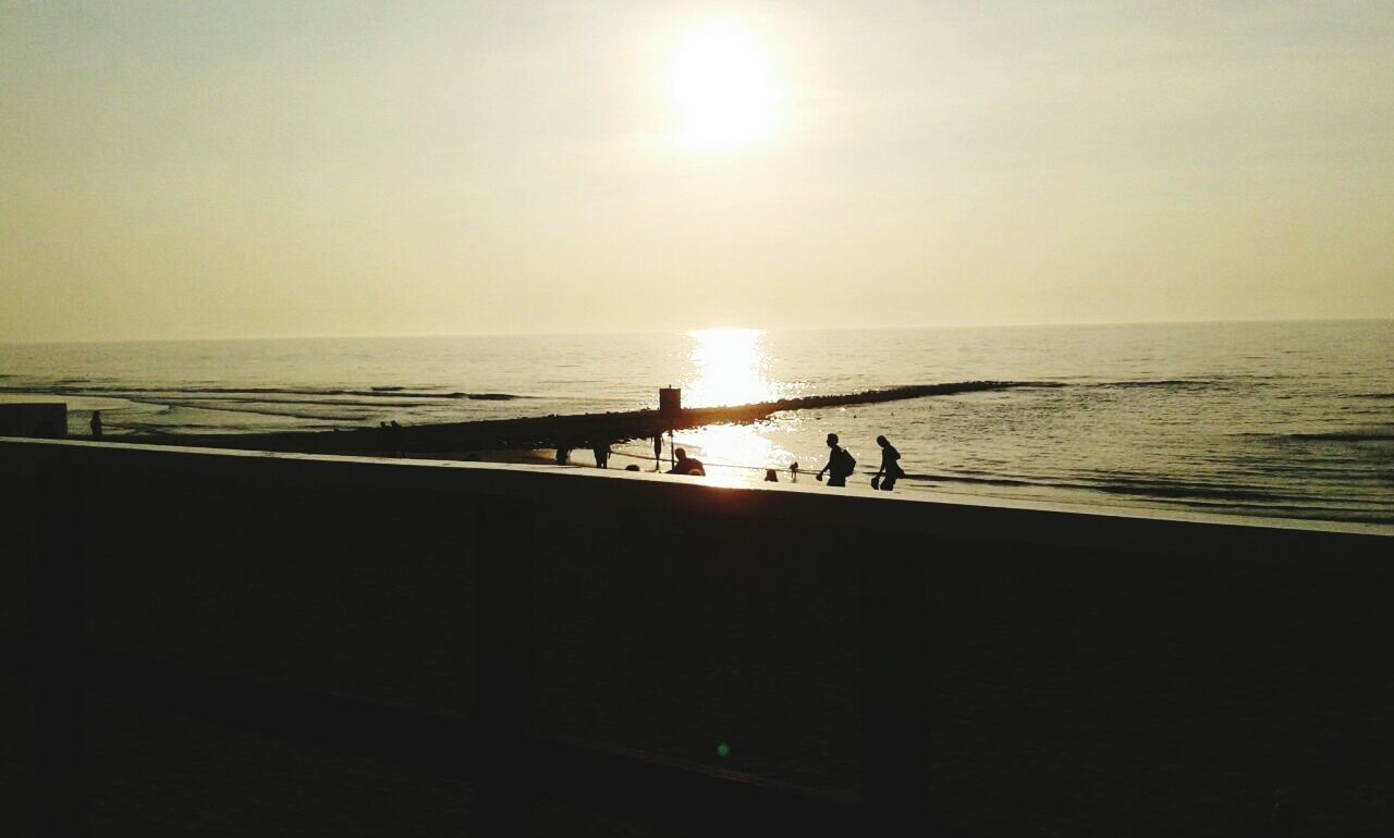 sea, water, horizon over water, silhouette, beach, scenics, sunset, nature, sun, tranquility, real people, tranquil scene, leisure activity, beauty in nature, clear sky, sky, sunlight, outdoors, men, sand, standing, lifestyles, vacations, togetherness, day, people