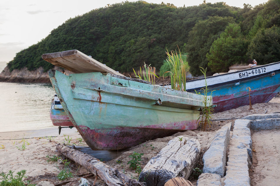 Old boats Beach Blue Boat Coastline Nature Old Man Sitting Outdoors Remote Sea Shore Tranquil Scene Tranquility Water