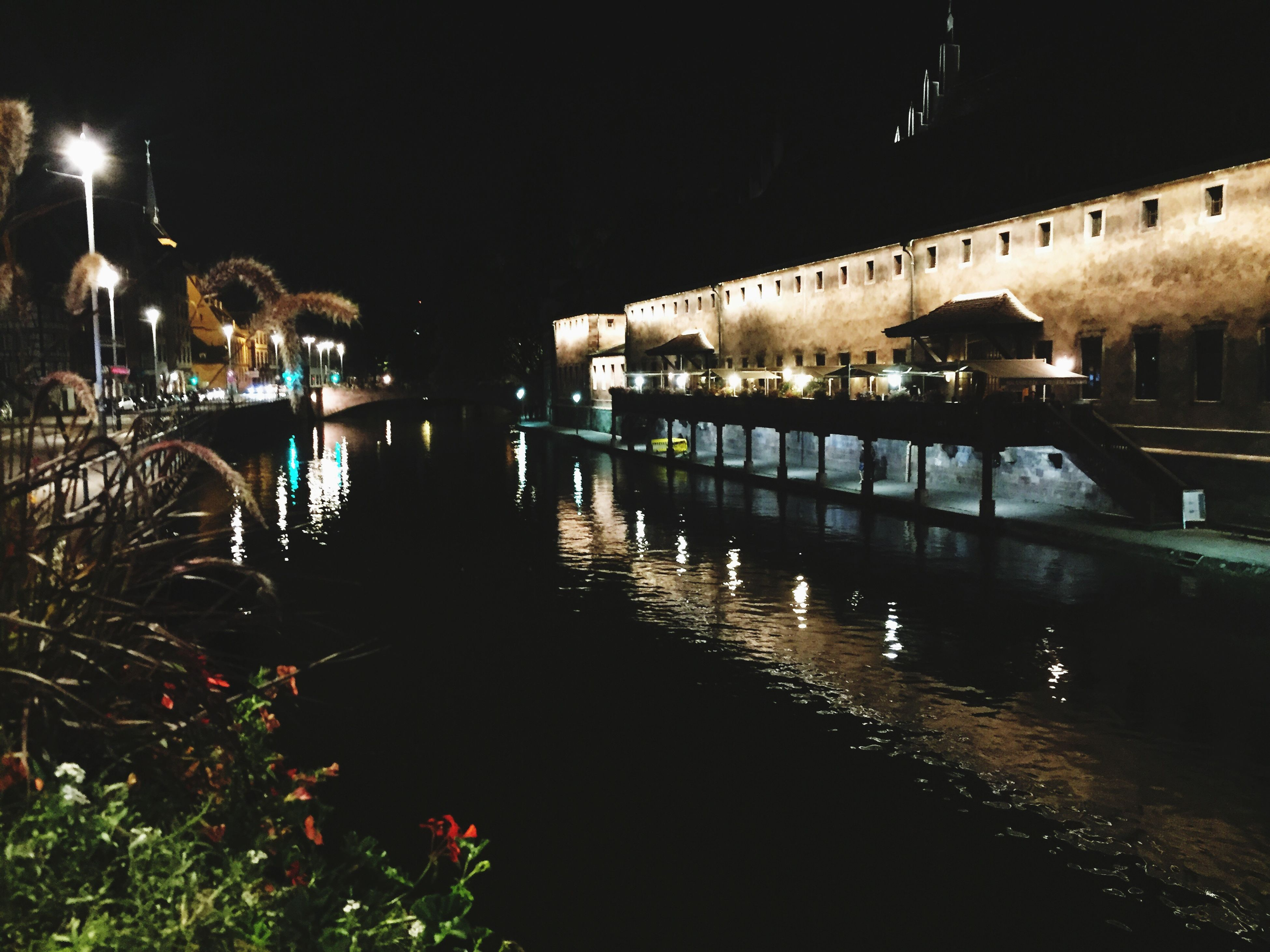 water, illuminated, night, reflection, architecture, building exterior, waterfront, tranquility, sky, calm, in a row, tranquil scene, scenics, outdoors, standing water, no people, footpath