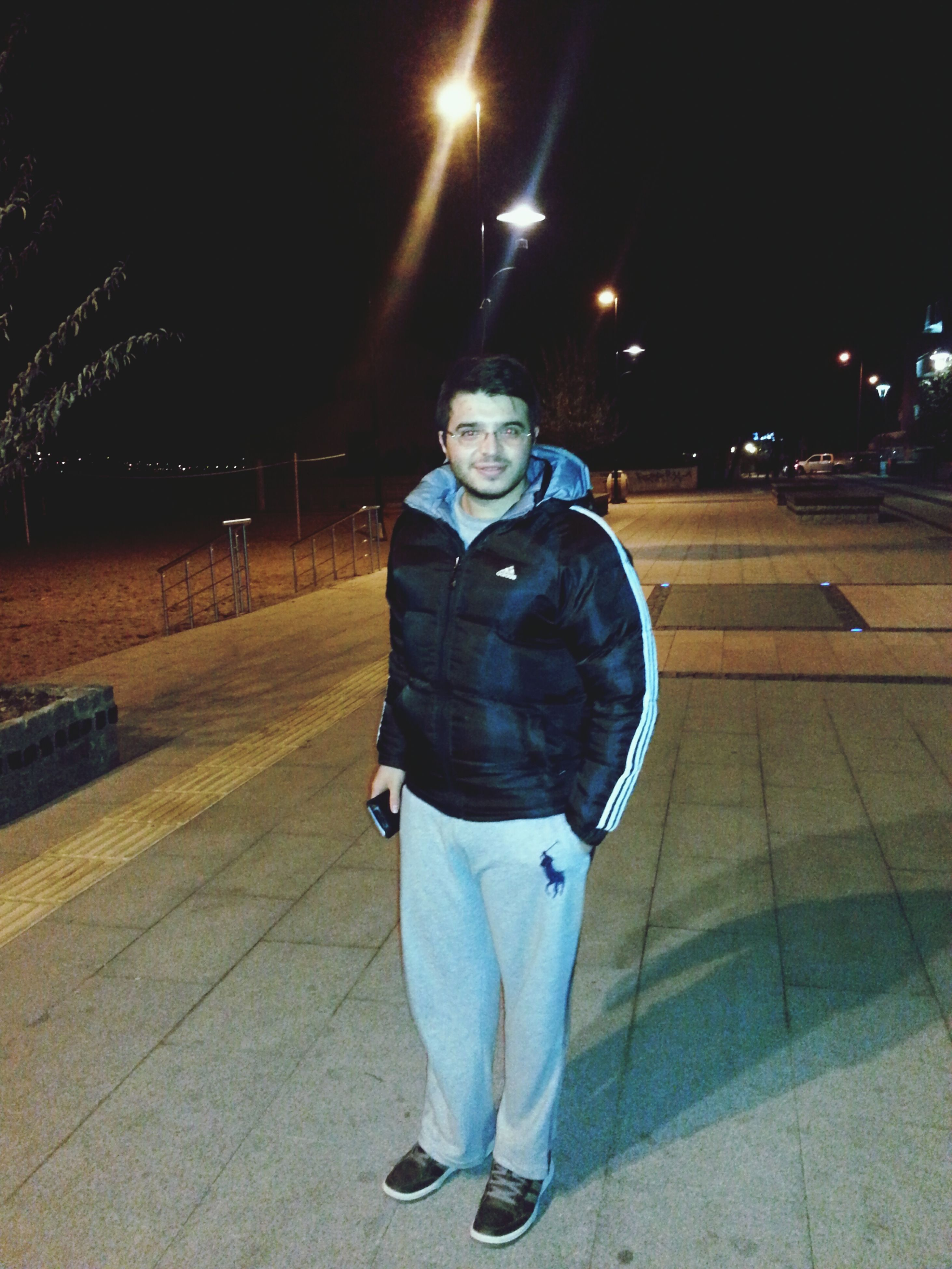 night, illuminated, full length, lifestyles, street, casual clothing, leisure activity, standing, rear view, front view, walking, men, road, outdoors, transportation, sidewalk, incidental people, holding