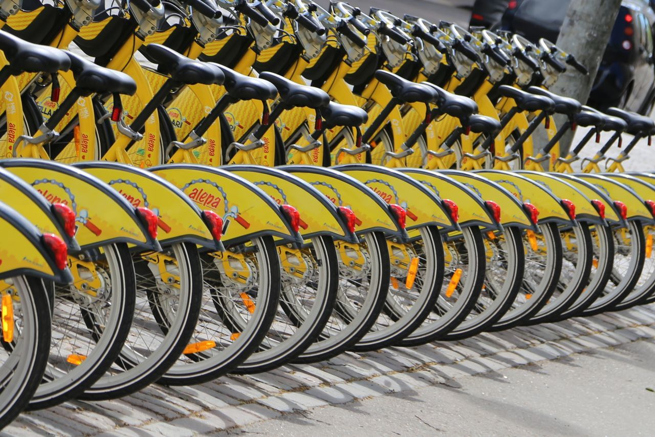 in a row, outdoors, day, bicycle rack, large group of objects, stationary, transportation, no people, close-up
