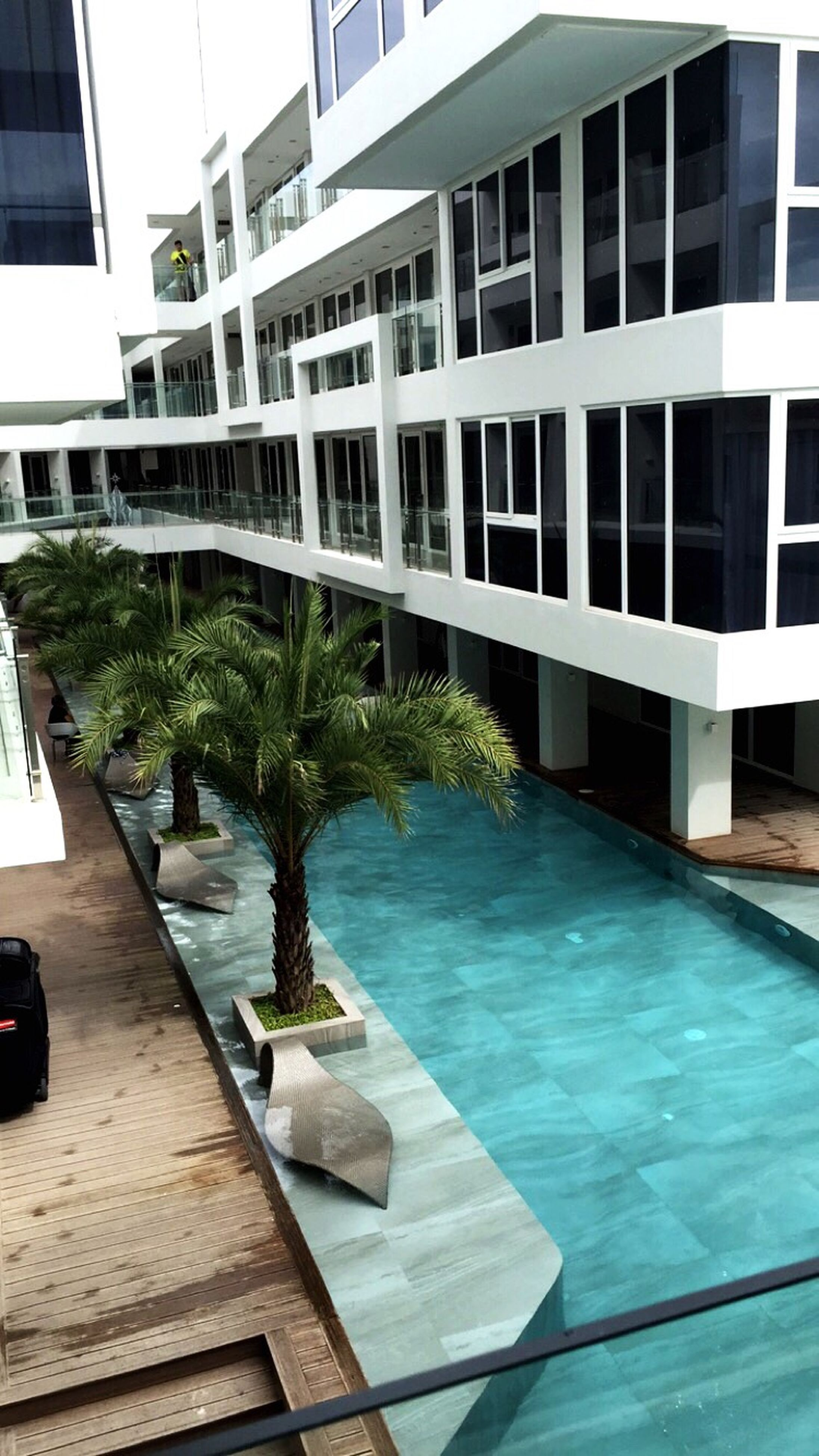 architecture, building exterior, built structure, swimming pool, water, reflection, window, glass - material, building, sunlight, city, day, residential building, table, tree, high angle view, house, no people, chair, outdoors