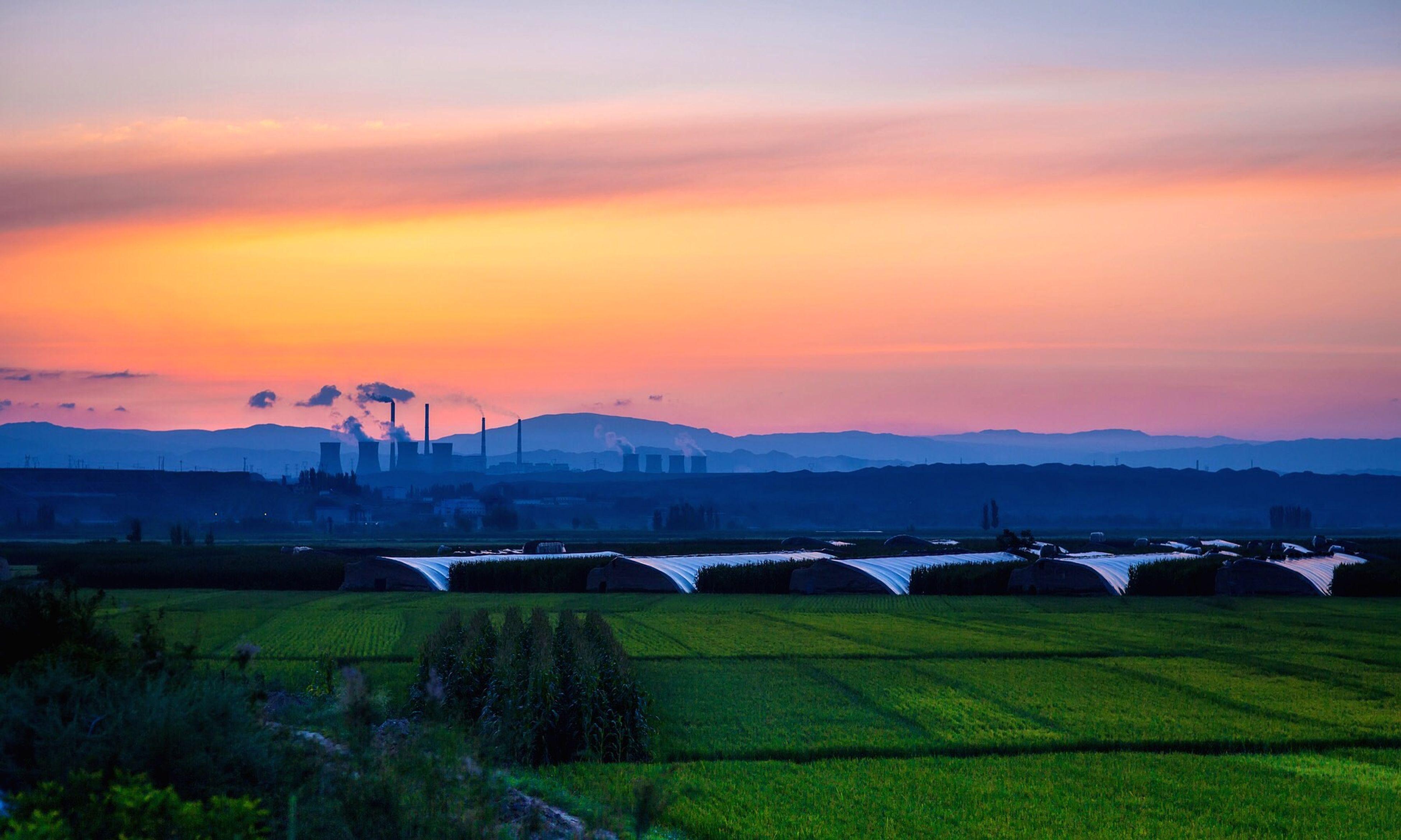 sunset, orange color, sky, mountain, landscape, scenics, field, cloud - sky, beauty in nature, tranquil scene, nature, tranquility, transportation, rural scene, grass, agriculture, mountain range, mode of transport, farm, idyllic