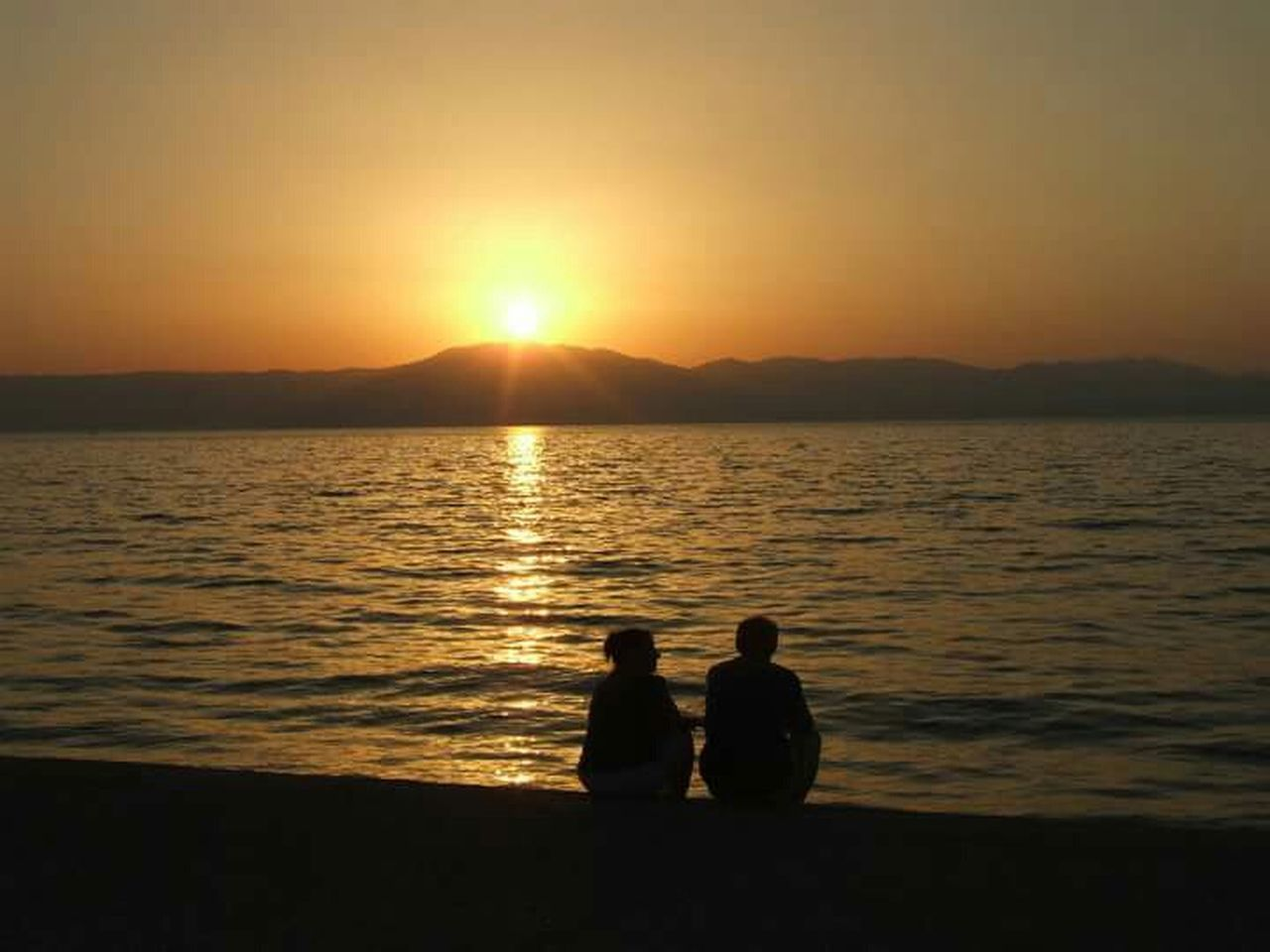 sunset, two people, silhouette, togetherness, beauty in nature, sun, scenics, nature, tranquil scene, tranquility, water, sitting, idyllic, men, sea, sunlight, real people, sky, bonding, couple - relationship, women, mountain, friendship, outdoors, clear sky, people
