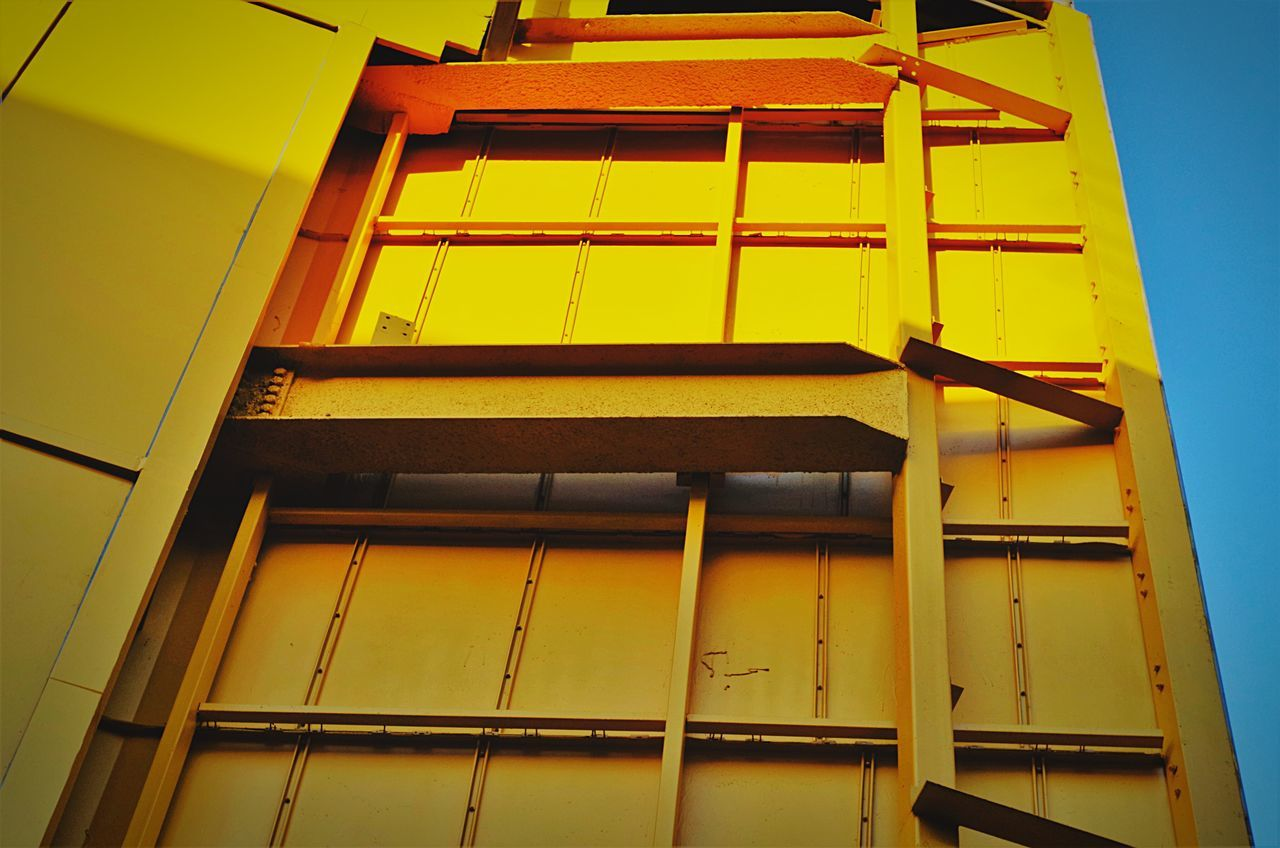 architecture, built structure, low angle view, yellow, no people, building exterior, outdoors, day, sky