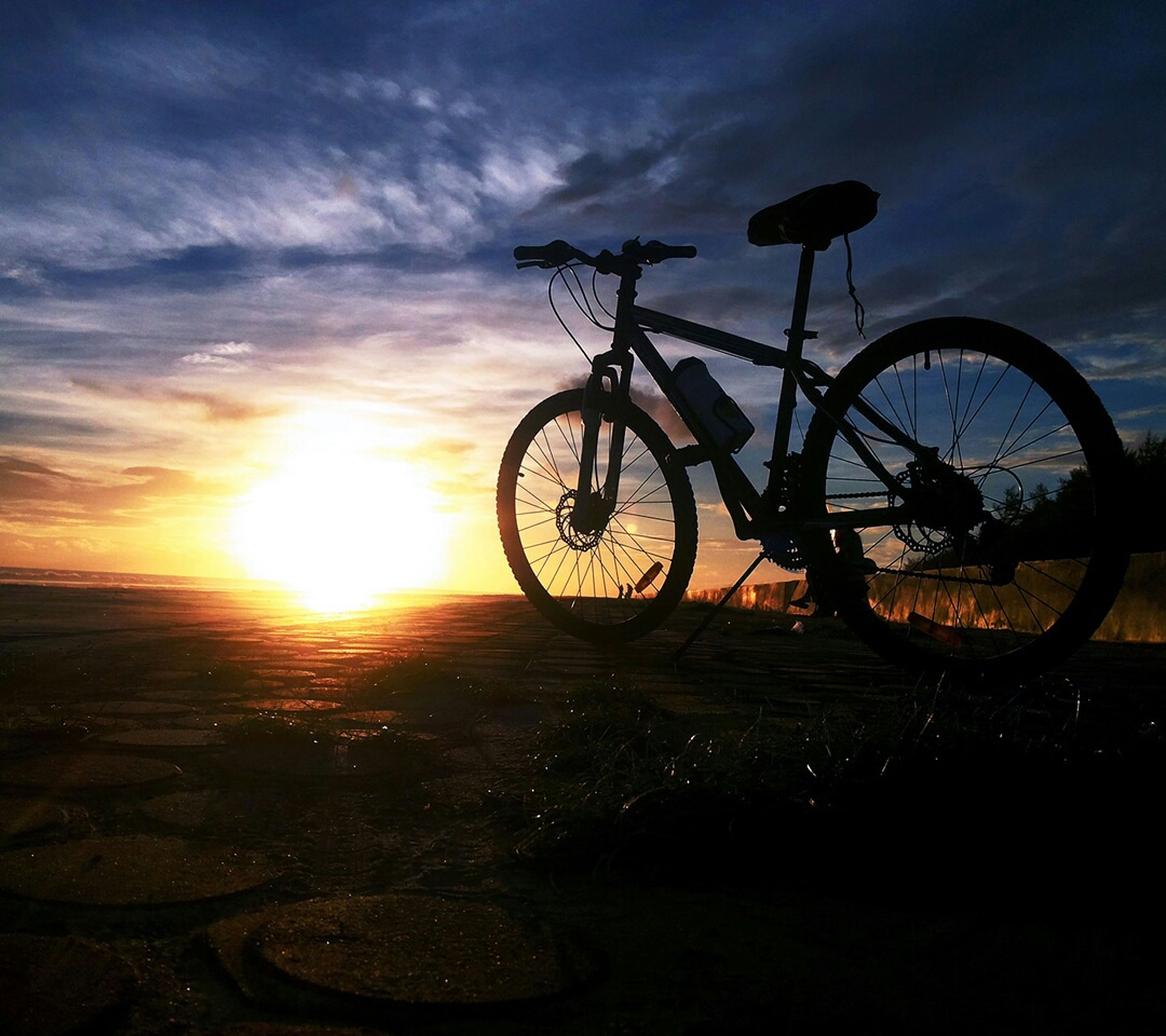 bicycle, sunset, transportation, land vehicle, sky, silhouette, sun, mode of transport, stationary, cloud - sky, parking, sunlight, orange color, parked, nature, tranquility, scenics, beauty in nature, wheel, tranquil scene