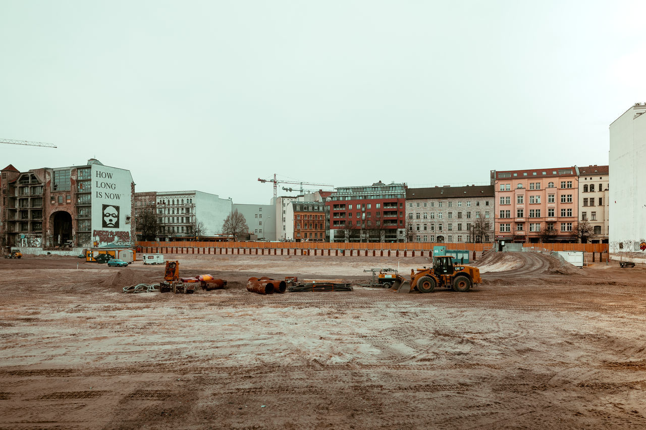 Earth Mover At Construction Site By Buildings Against Sky