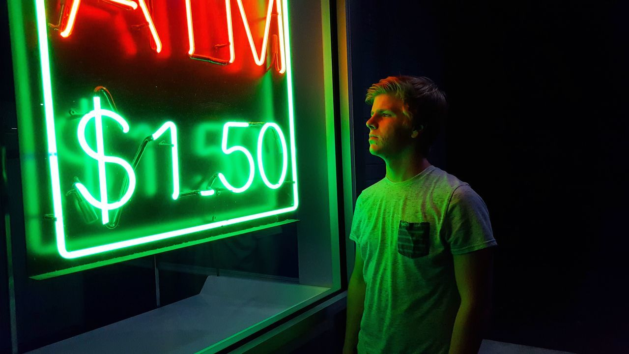 illuminated, green color, one person, night, standing, real people, neon, young adult, indoors