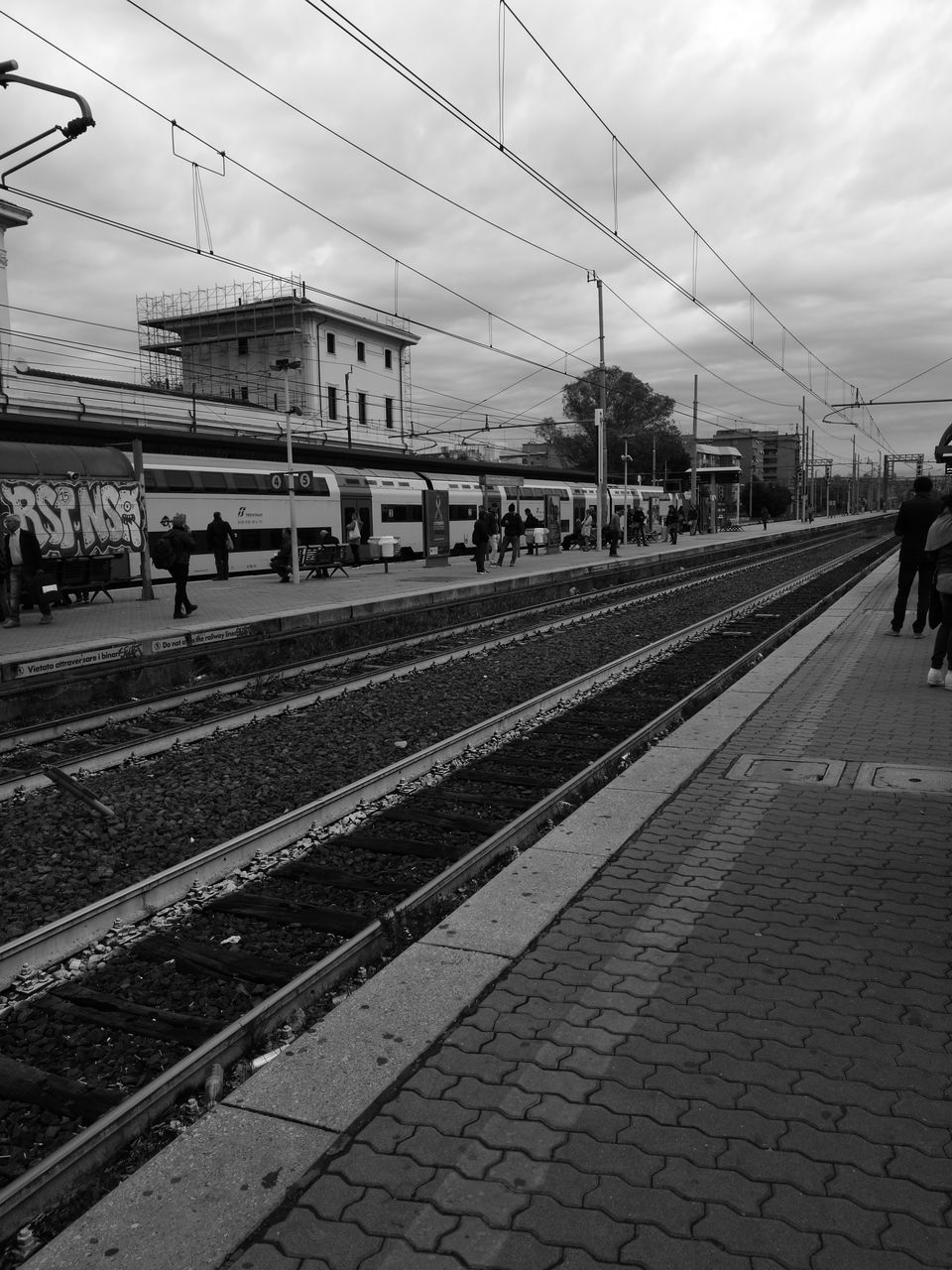 transportation, railroad track, rail transportation, real people, public transportation, railroad station platform, sky, cable, travel, railroad station, day, men, women, outdoors, architecture, large group of people, people