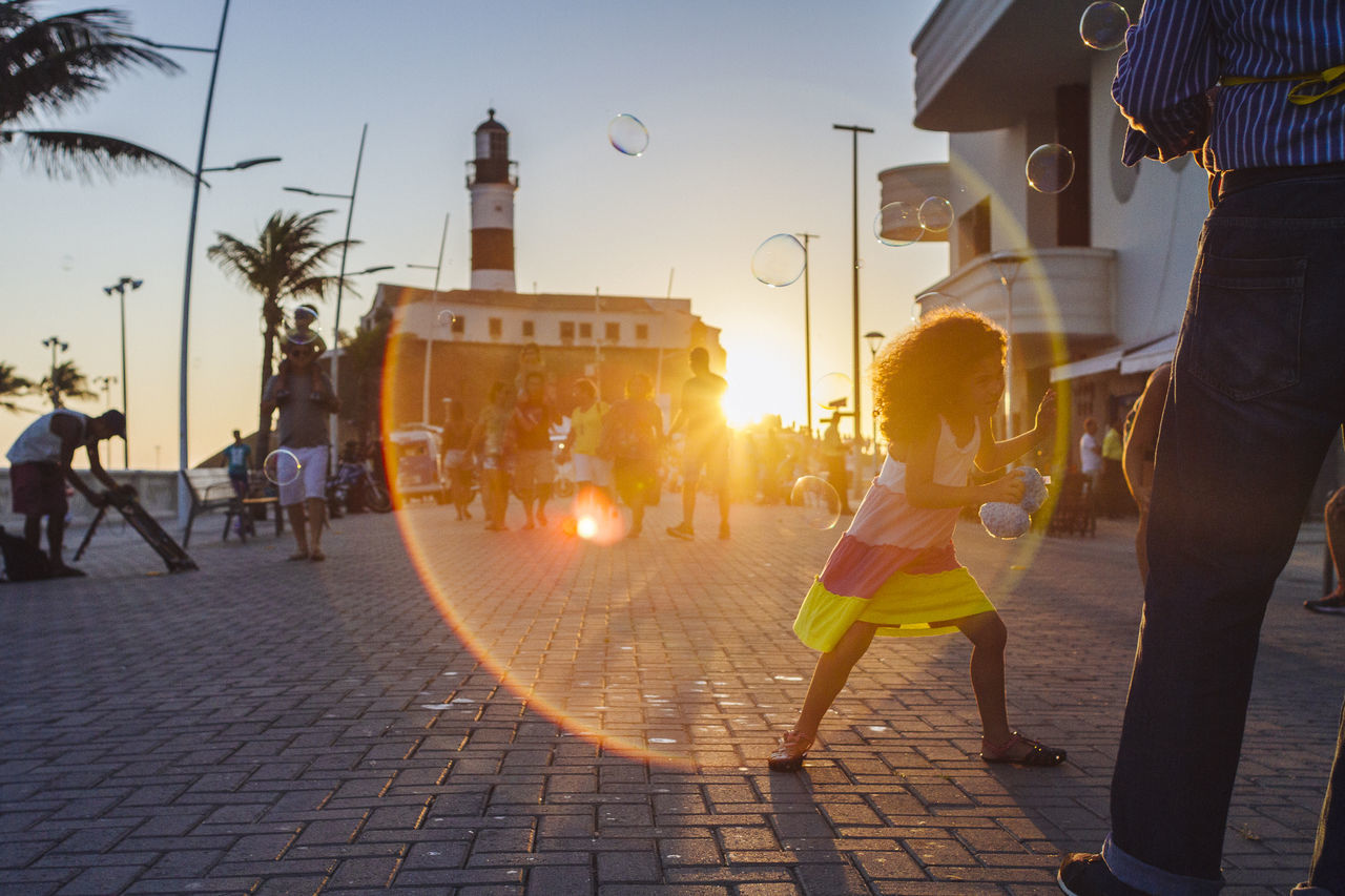 A beautiful girl plays with soap bubbles from a street vendor Bubble Wand Childhood City Full Length Hapiness Kids Being Kids Lens Flare Live For The Story Outdoors Real People Street Sun Sunbeam Sunlight Sunset The Street Photographer - 2017 EyeEm Awards Two People Walking