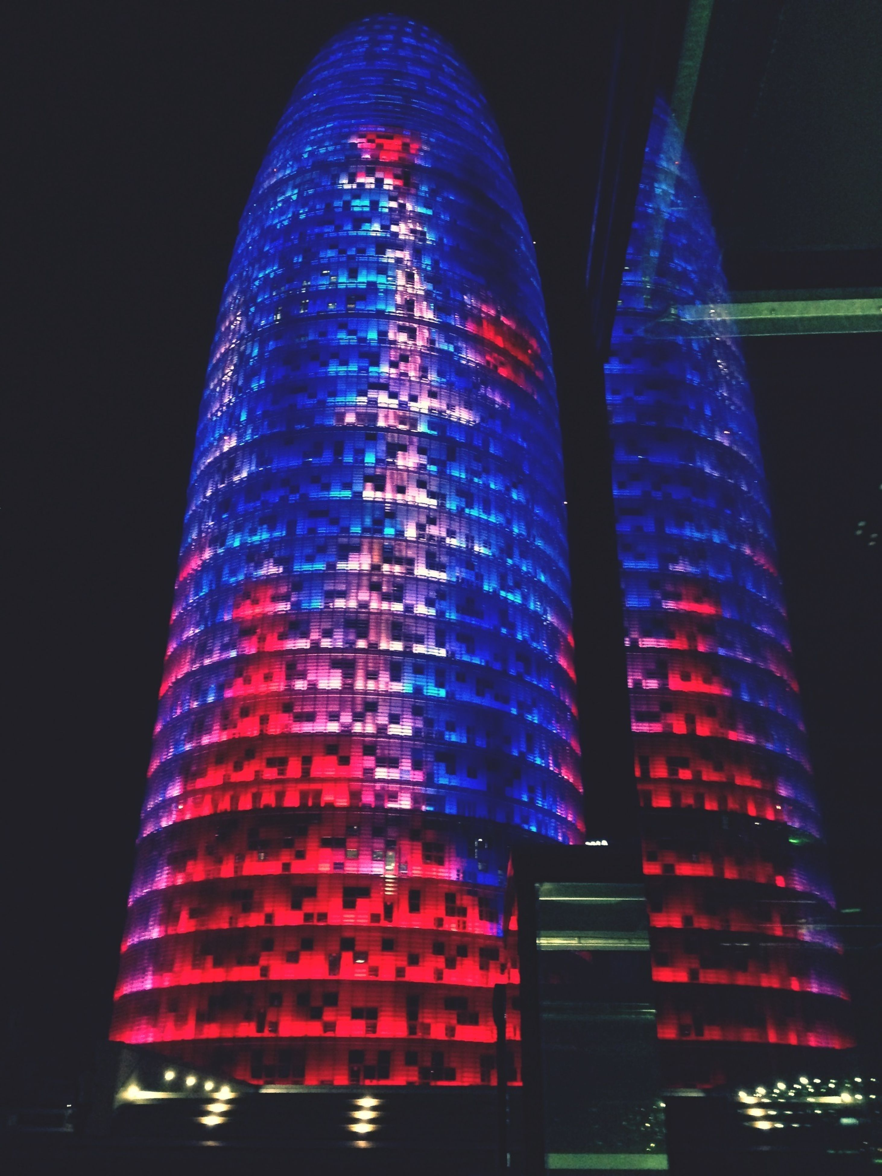 illuminated, night, architecture, building exterior, low angle view, built structure, red, modern, city, multi colored, lighting equipment, no people, reflection, pattern, glowing, skyscraper, tall - high, tower, light - natural phenomenon, outdoors