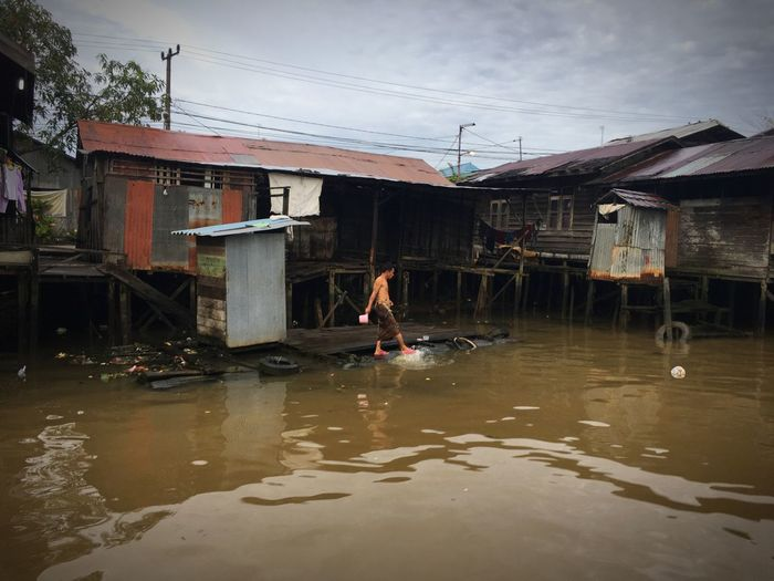 """""""Indonesia In My Eyes"""" Building Exterior Built Structure Architecture Water One Person Outdoors Day Real People Sky IPhoneography Iphone6splus Activity Banjarmasin Borneo"""