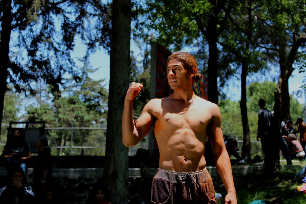 shirtless, real people, leisure activity, front view, lifestyles, one person, young adult, tree, outdoors, standing, day, young men, nature, young women