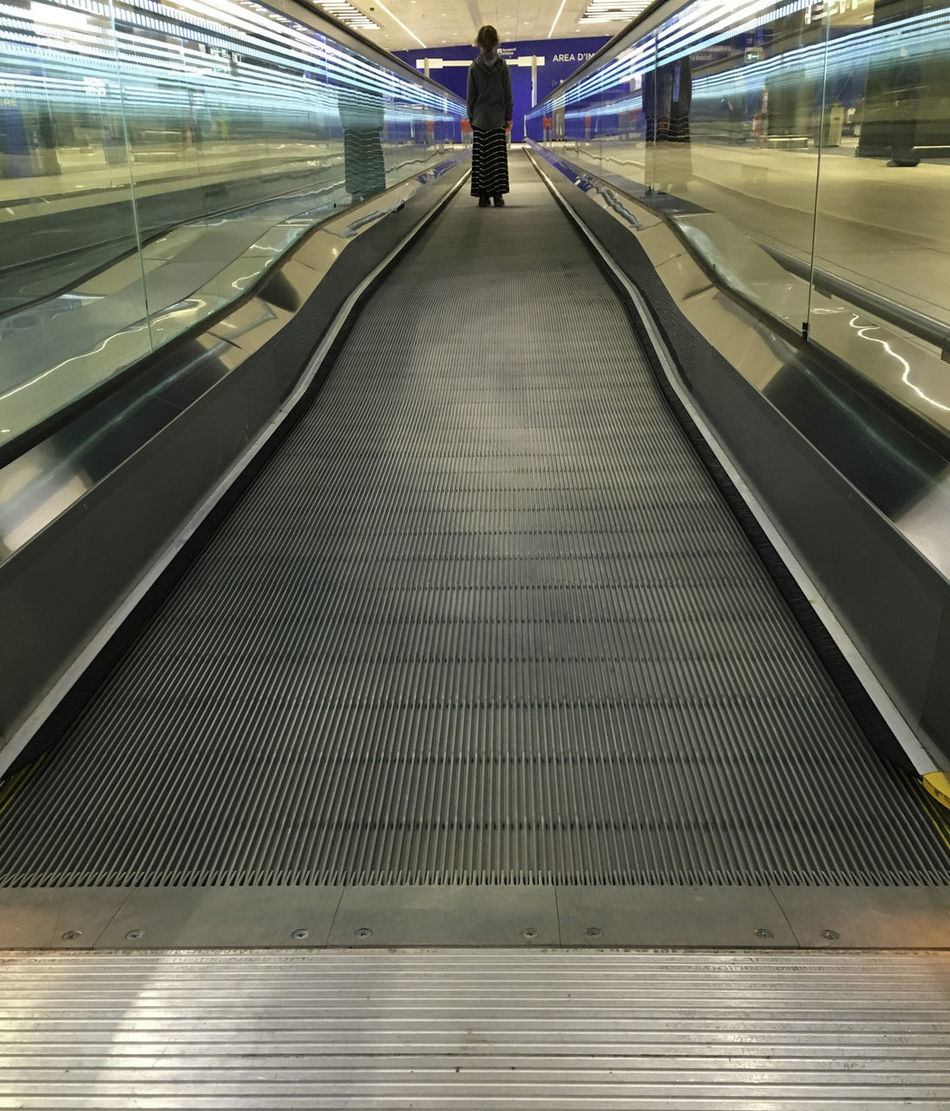 Girl on escalator Airport Convenience Escalator Girl Illuminated Modern Move Single Technology Transportation