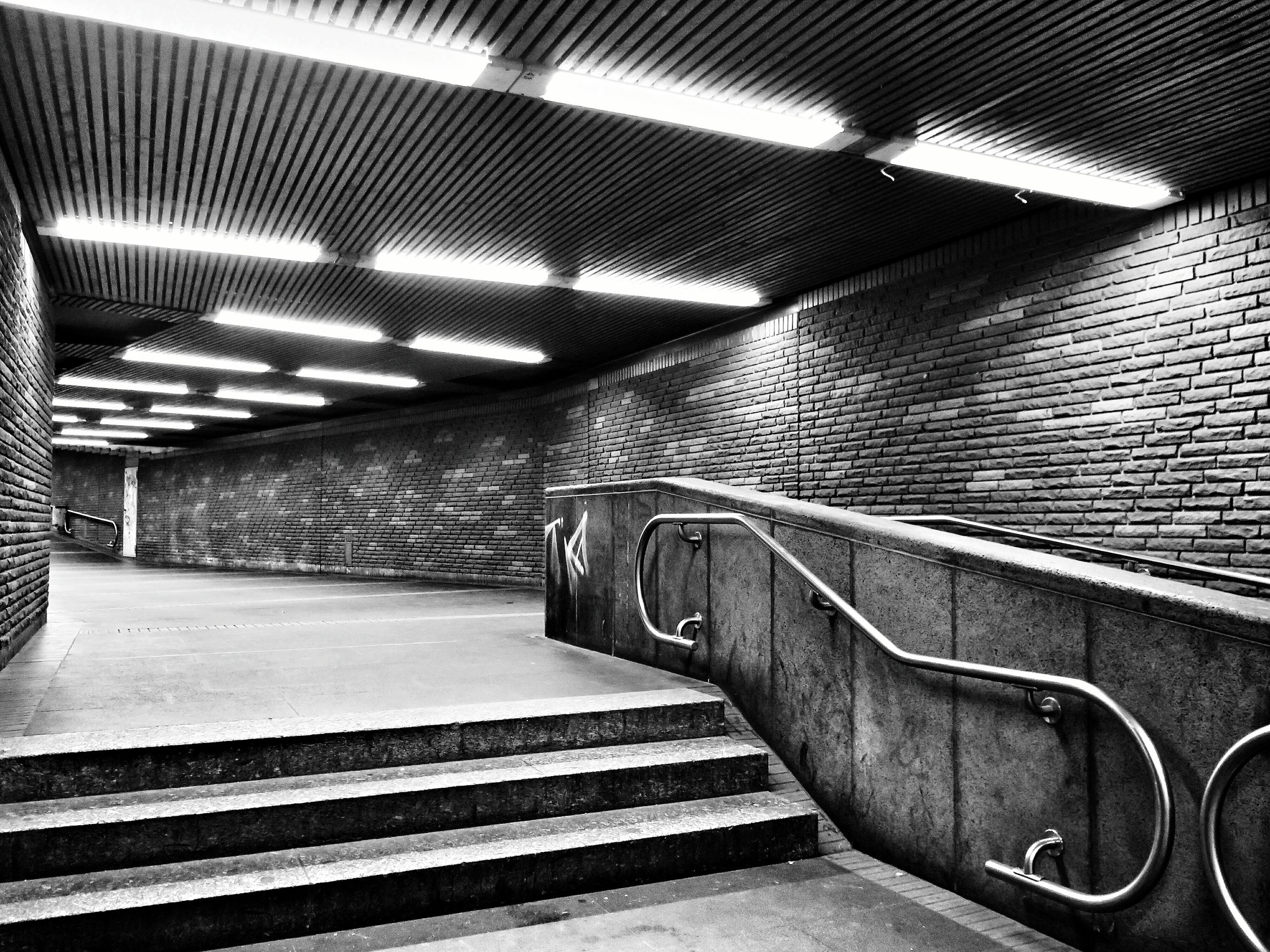 indoors, steps and staircases, steps, the way forward, staircase, railing, empty, absence, high angle view, transportation, diminishing perspective, architecture, built structure, wall - building feature, vanishing point, illuminated, tunnel, escalator, no people, ceiling