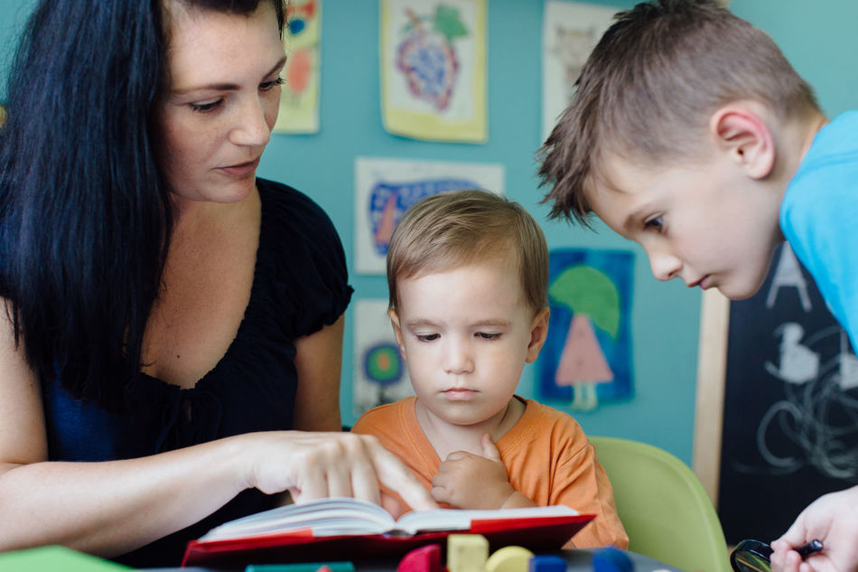 Mother reading a book to her children Book Brothers Caucasian Childhood Children Education Family Home Homeschooling Kids Learn Learning Mother Mother And Children Parent Reading Reading A Book Siblings Skills  Story Storytelling Storytime Study Three People Togetherness