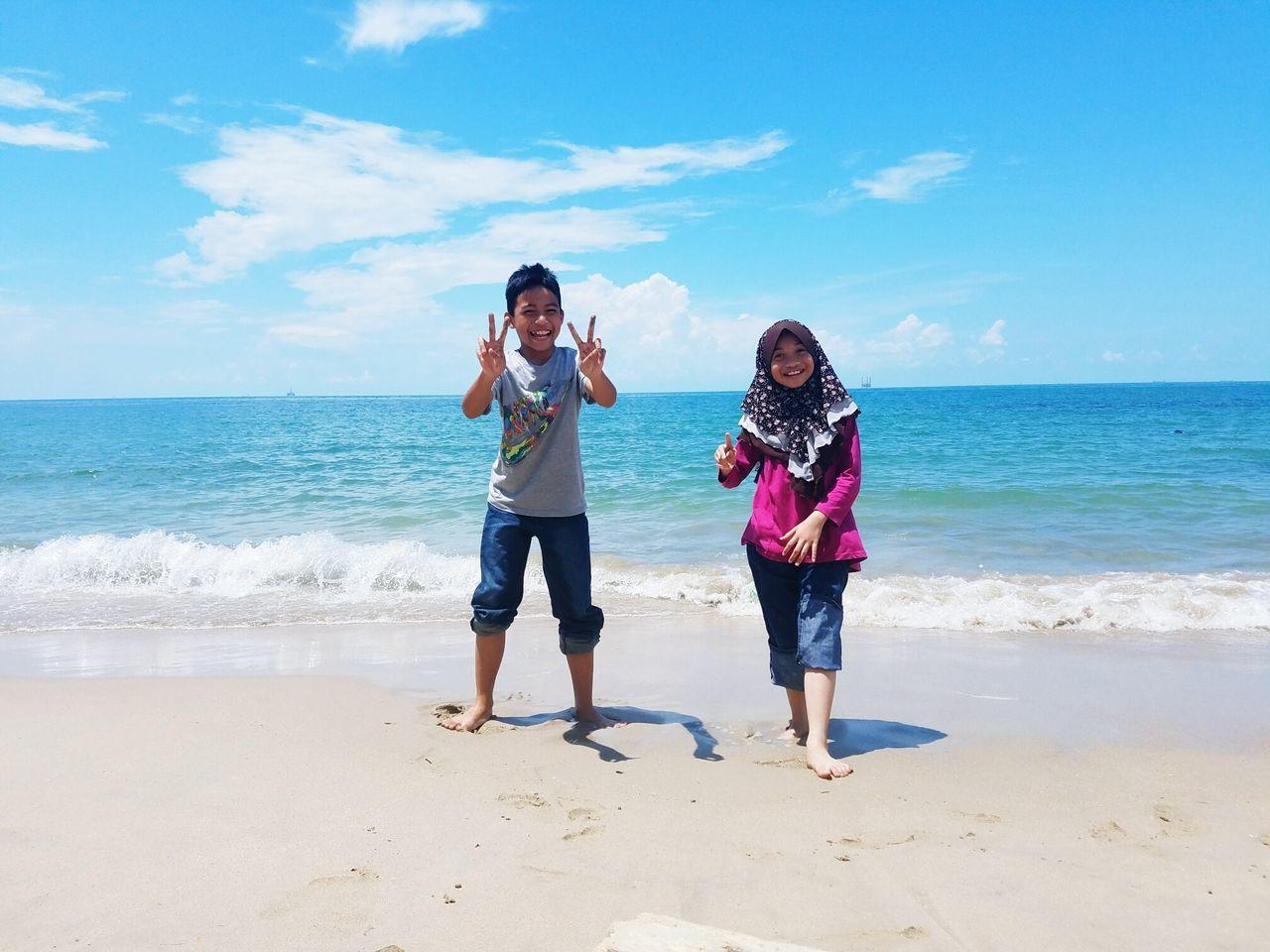 Portrait Of Happy Siblings Gesturing While Standing At Beach Against Sky