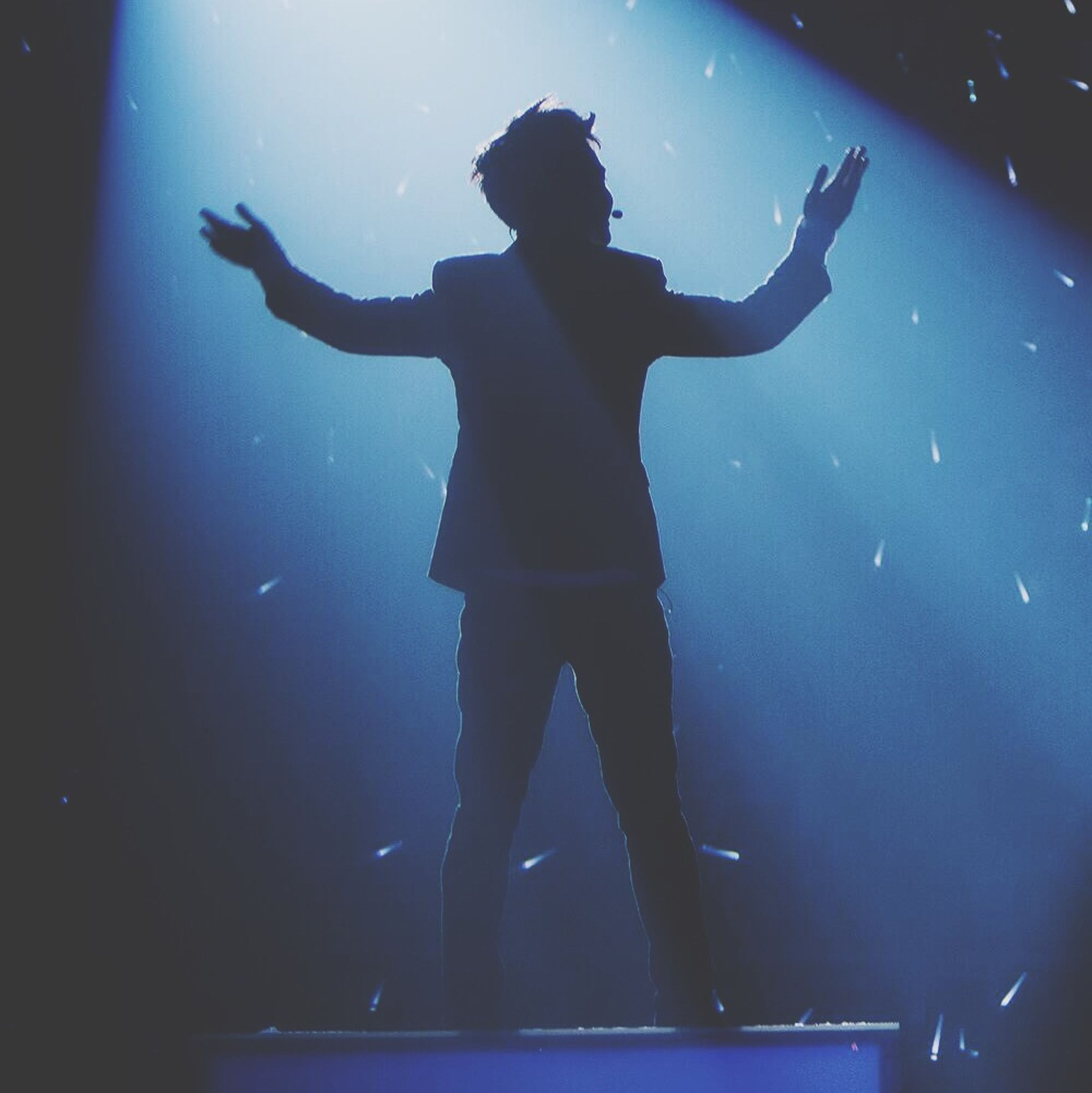 lifestyles, leisure activity, full length, enjoyment, fun, night, arms raised, silhouette, men, standing, indoors, jumping, arms outstretched, low angle view, carefree, illuminated, playing, blue