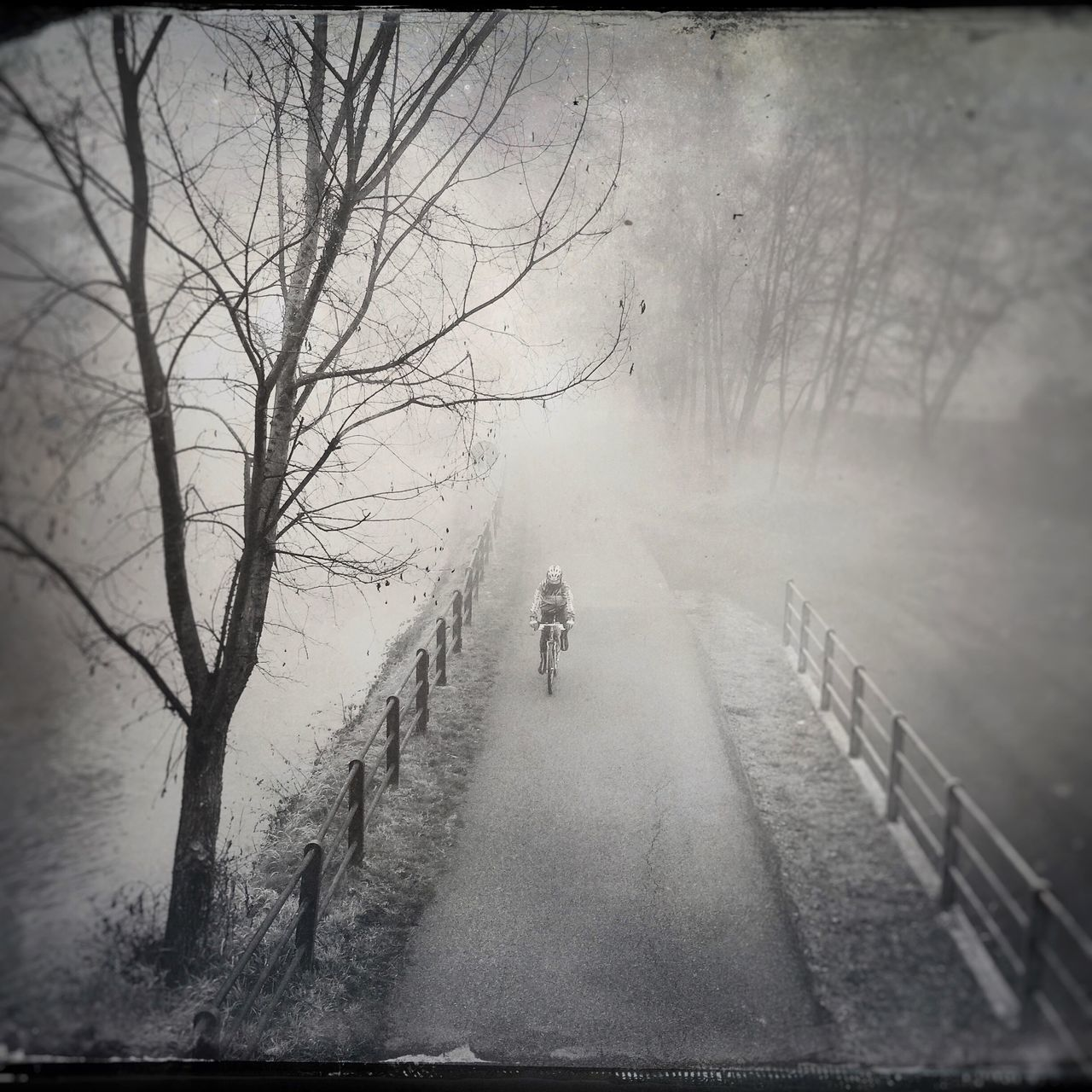 High Angle View Of Person Riding Bicycle On Footpath During Foggy Weather