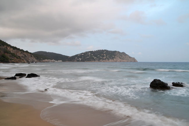 Landscape of Aigues Blanques beach in Ibiza, Spain Aigues Blanques Balearic Islands Beach Beauty In Nature Cloud - Sky Coastline Horizon Over Water Ibiza Idyllic Illes Balears Islas Baleares Nature Ocean Outdoors Picturesque Rock Rock - Object Scenics Sea Shore Tourism Tranquil Scene Travel Water Wave