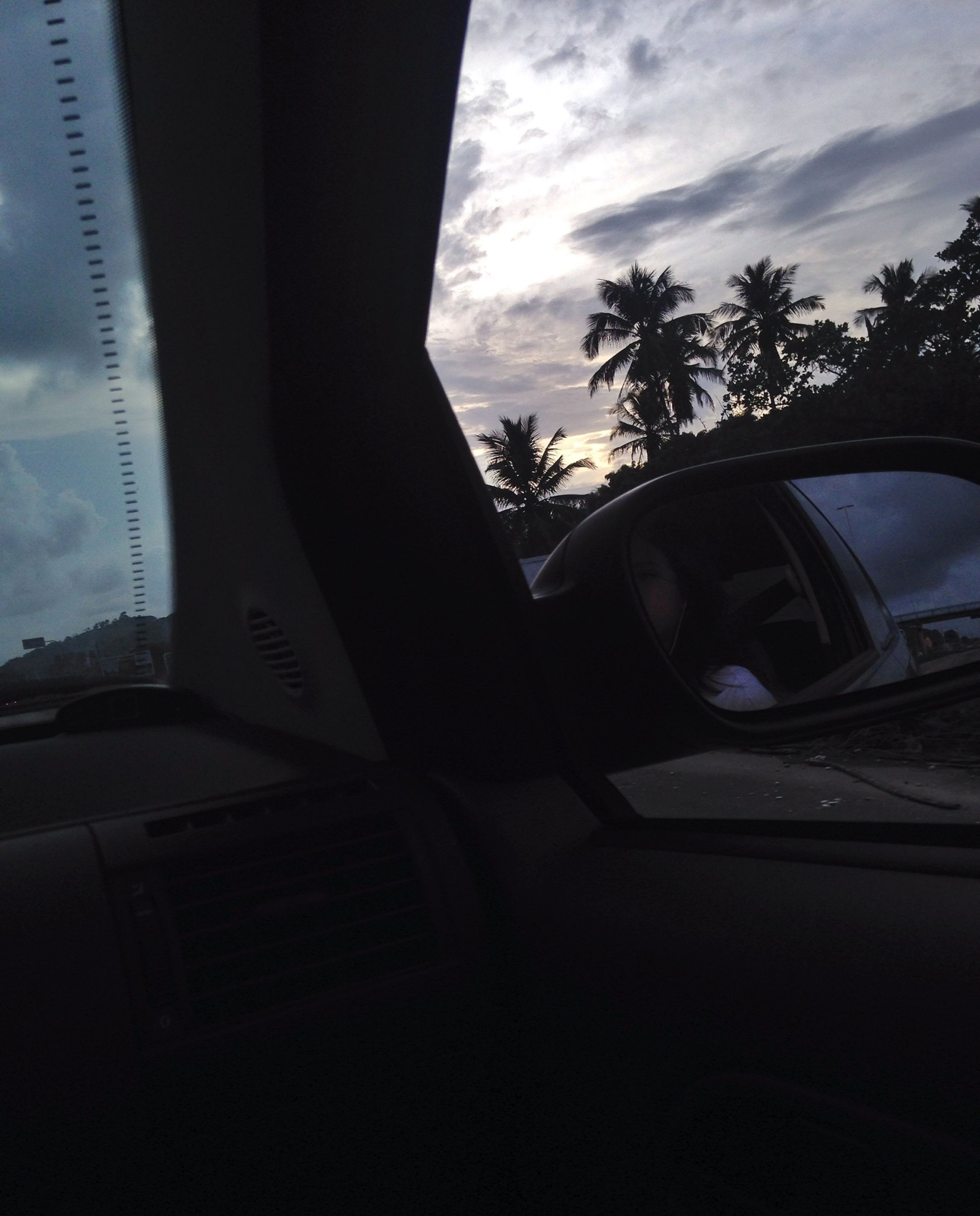 transportation, sky, mode of transport, car, land vehicle, cloud - sky, architecture, built structure, tree, building exterior, glass - material, window, cloud, low angle view, silhouette, vehicle interior, transparent, road, city, travel