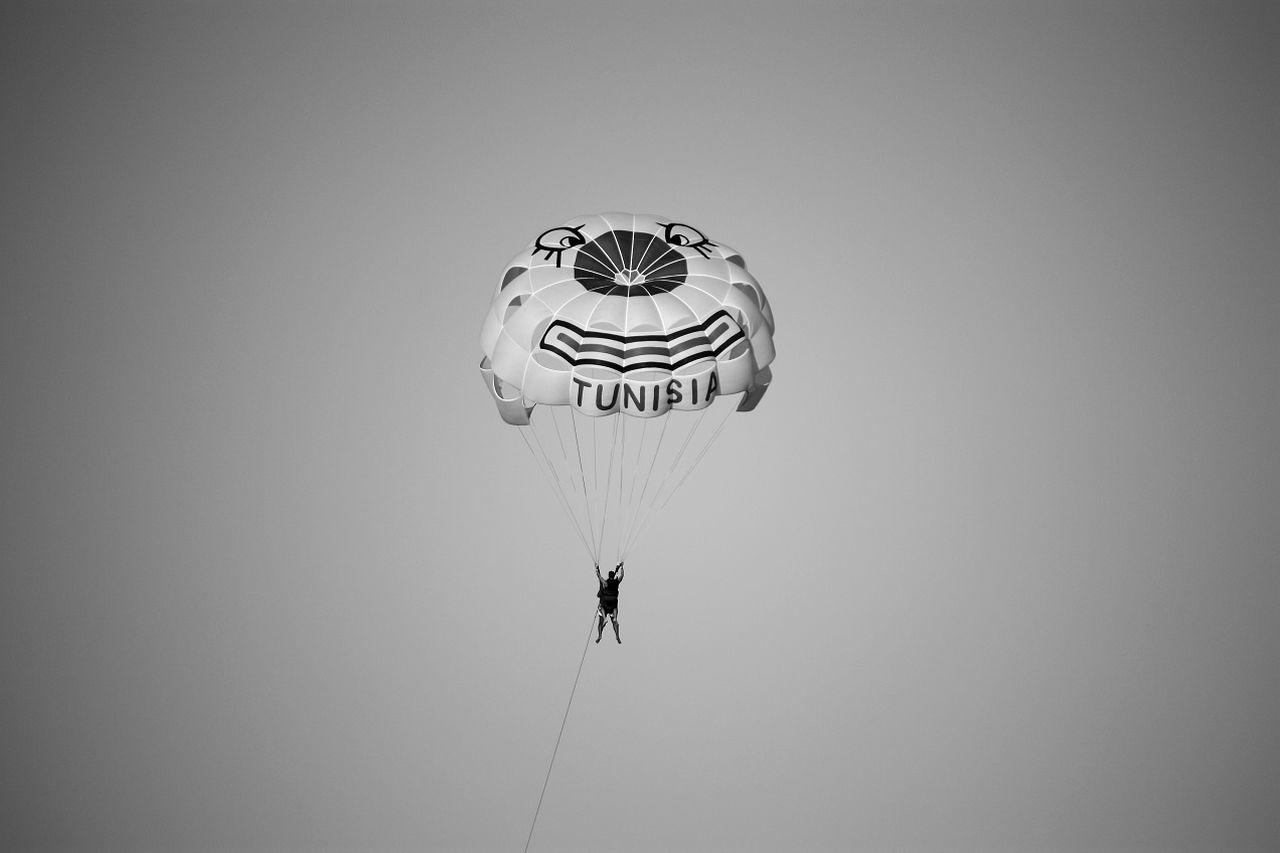 low angle view, parachute, mid-air, real people, adventure, one person, day, outdoors, men, extreme sports, sky, people